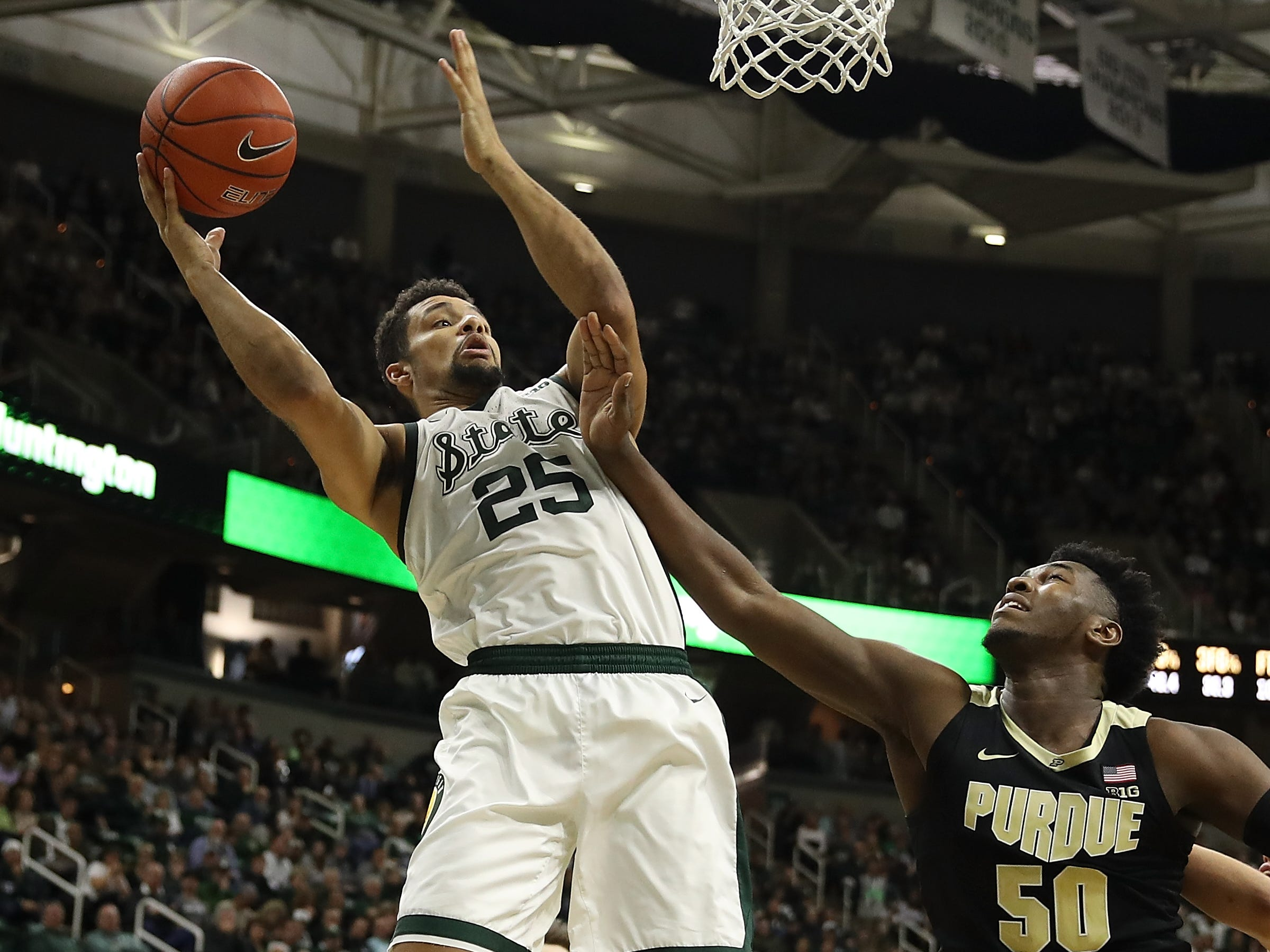 Kenny Goins #25 of the Michigan State Spartans gets a shot off next to Trevion Williams #50 of the Purdue Boilermakers during the first half at Breslin Center on January 08, 2019 in East Lansing, Michigan.