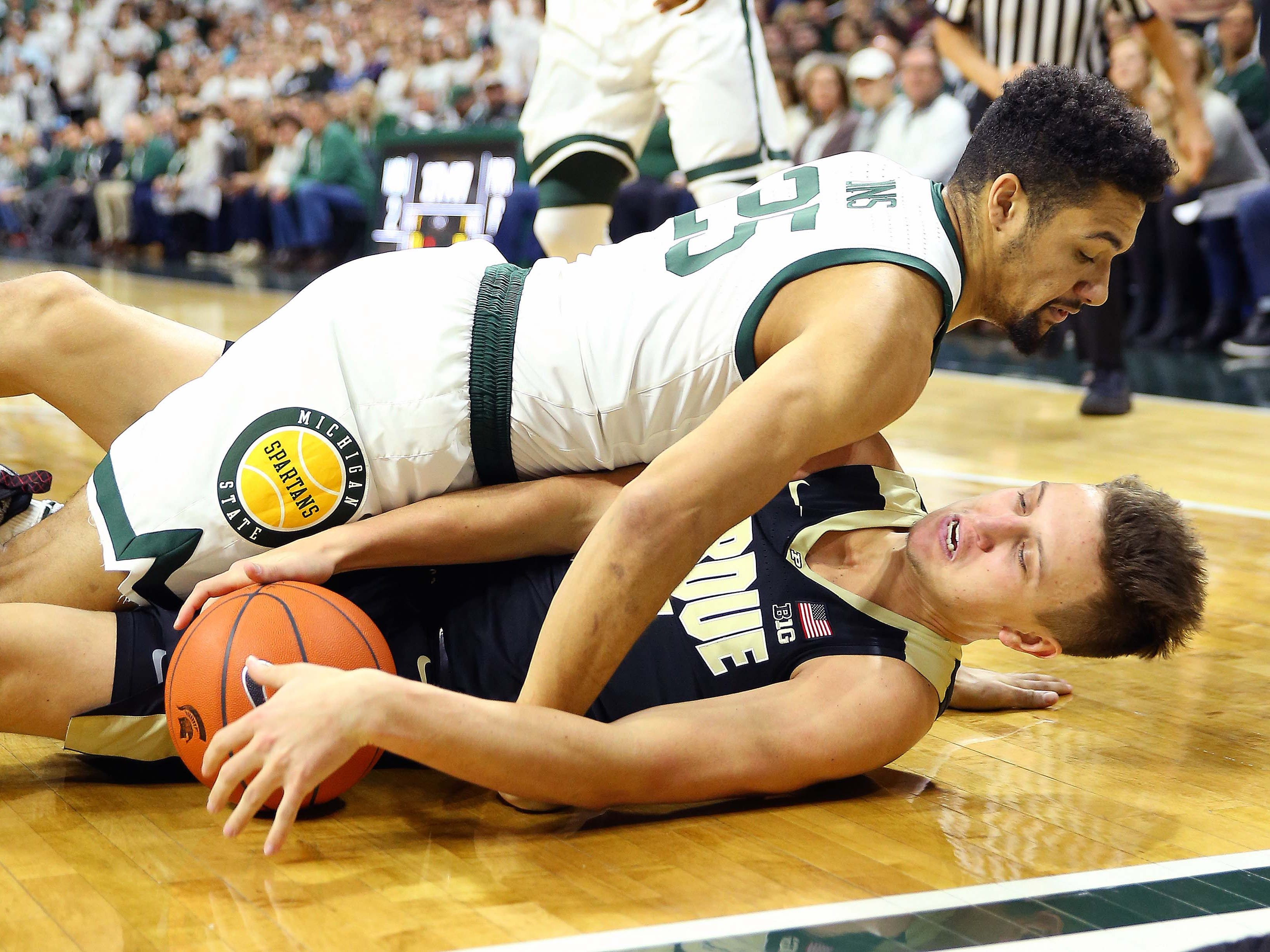 Purdue Boilermakers forward Aaron Wheeler (1) and Michigan State Spartans forward Kenny Goins (25) fight for a loose ball during the first half of a game at the Breslin Center.