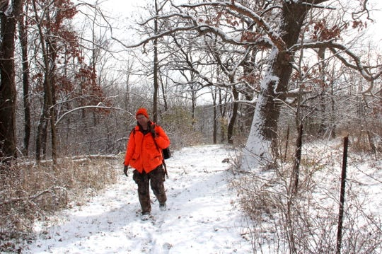 A deer hunter returns to camp after a morning of hunting near Dodgeville, Wisconsin.