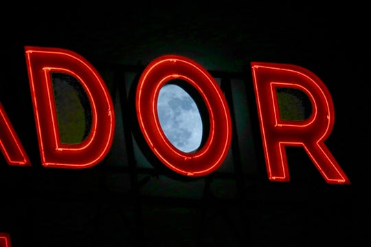 The moon rises behind the Ambassador Hotel neon sign on Wisconsin Avenue in Milwaukee Dec. 3, 2017.