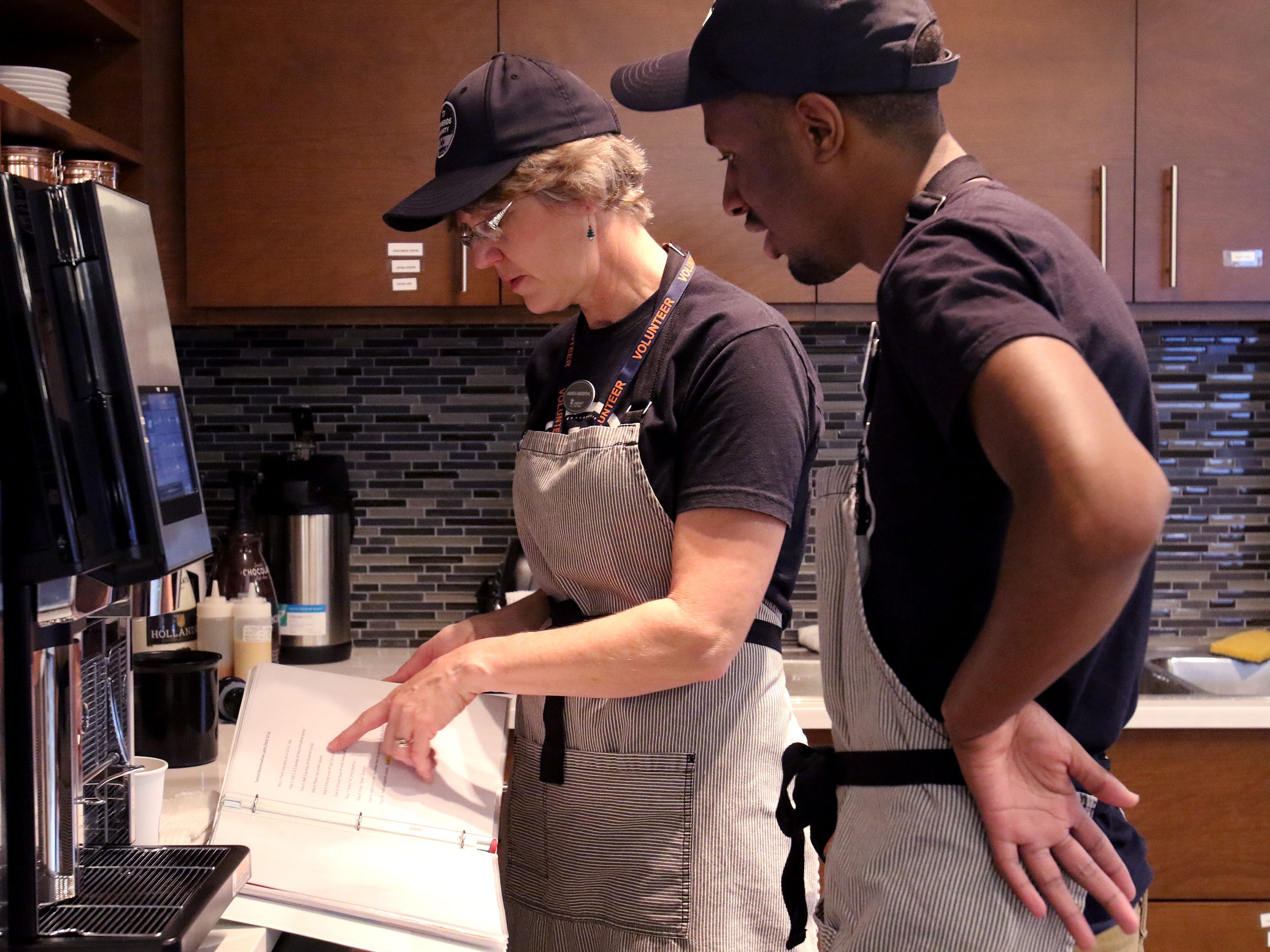 Volunteer Andrea Huedepuhl and Ben Page check the recipe for a customer's beverage order at Shepherds Community Cafe inside Community State Bank in Union Grove on Dec. 20.