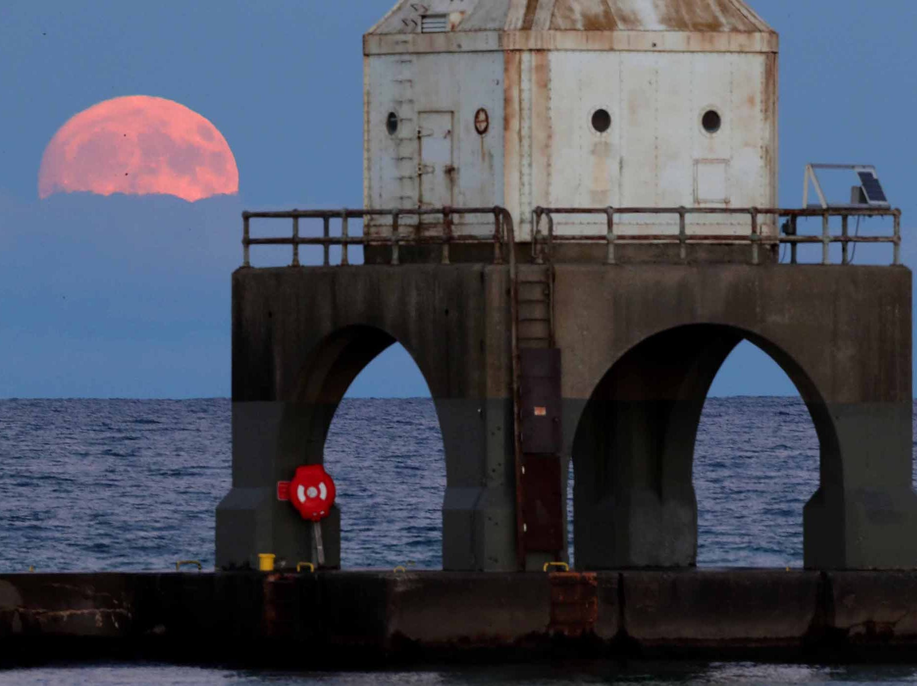 A nearly full waxing gibbous moon, at 99.4% full, rises over Lake Michigan behind the Port Washington breakwater lighthouse on Oct. 23, 2018.