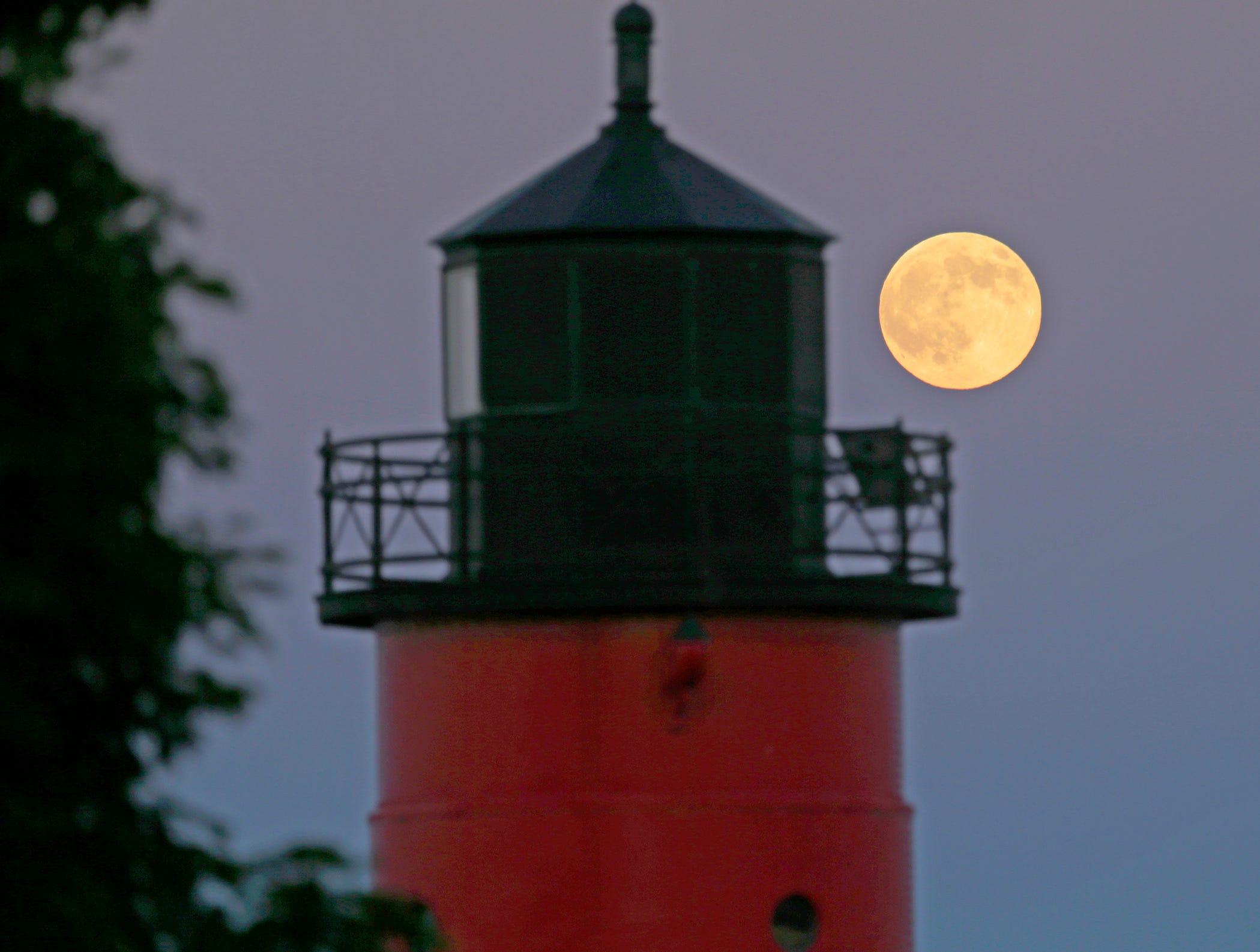 The moon rises near the Milwaukee Pierhead Light off the Summerfest grounds on July 9, 2017.