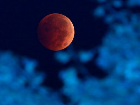 The blood moon is seen from near Milwaukee on Oct. 8, 2014. A blood moon occurs when a total lunar eclipse turns the moon a reddish color.