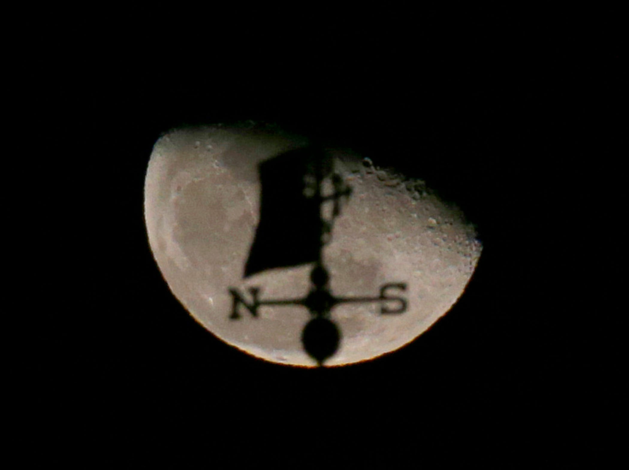 The moon is seen behind a weathervane above Sendik's Food Market in Bayside  Dec. 18, 2016.