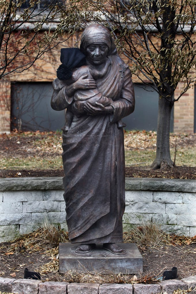 A statue of Mother Teresa of Calcutta stands on the campus of Marquette University. Someone took the liberty to place a knit hat on the baby she is holding.