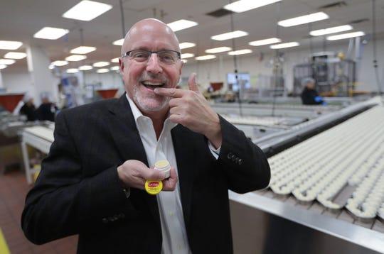 Paul Woelbing, president of Carma Laboratories Inc., applies Carmex in the jar room at Carma Laboratories Inc. in Franklin.