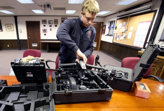 Merton Firefighter Josh Paral packs the department's new drone into three cases that are stored in a department support vehicle.