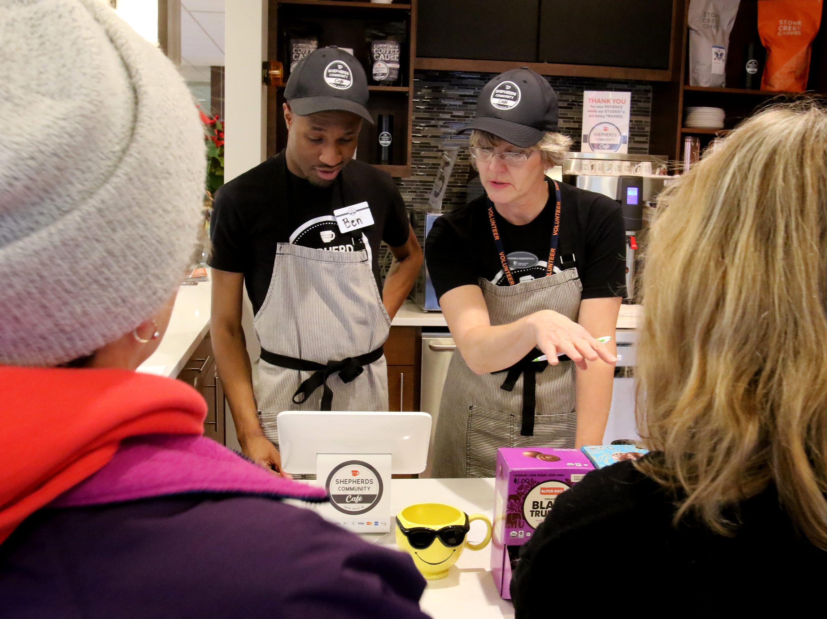 Volunteer Andrea Huedepuhl works with Ben Page on taking customer orders at Shepherds Community Cafe inside Community State Bank in Union Grove on Dec. 20.