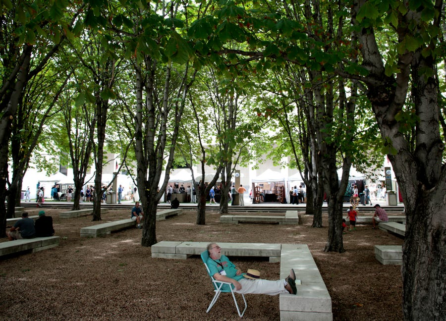 A man naps under the chestnut trees next to the Marcus Center for Performing Arts on the last day of the Morning Glory Fine Craft Fair on Aug.  12, 2012.