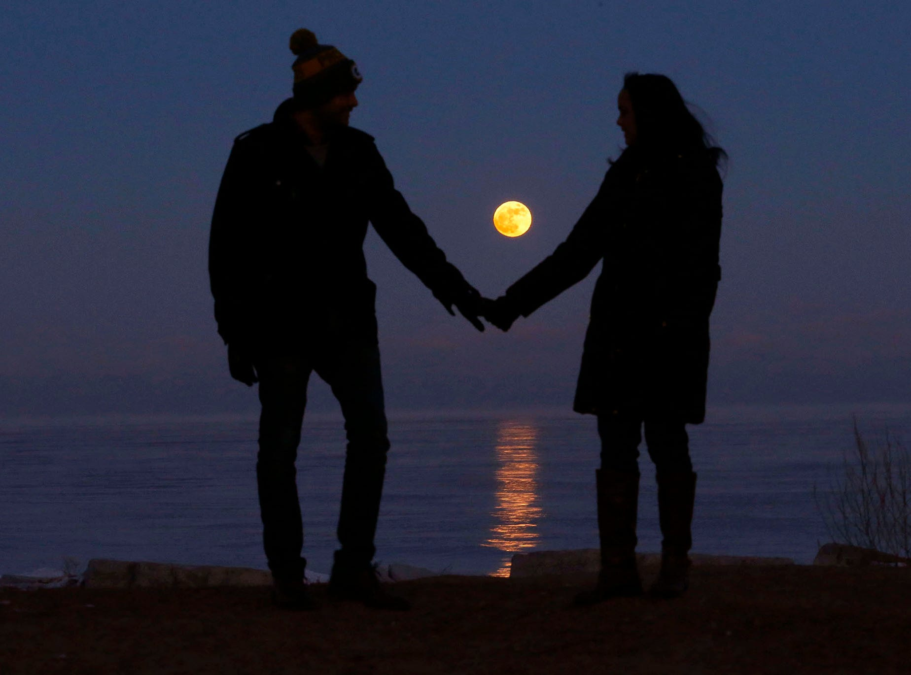 Badrinath Uppalapati, left, and his girlfriend, Bhargavi Tadinada, both from Milwaukee, pause for a moment after checking out the supermoon off the shores of Lake Michigan near Bradford Beach in Milwaukee Jan. 1, 2018.