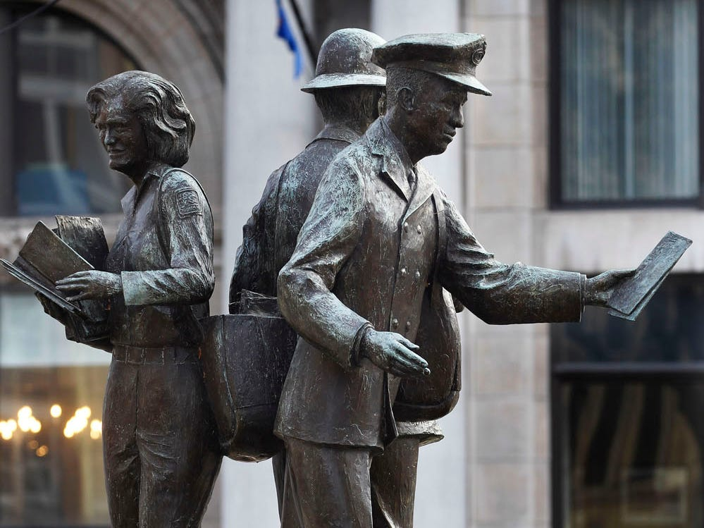 A statue honoring the work of letter carriers is Plankinton Avenue and Wells Street. On the left is a woman letter carrier.