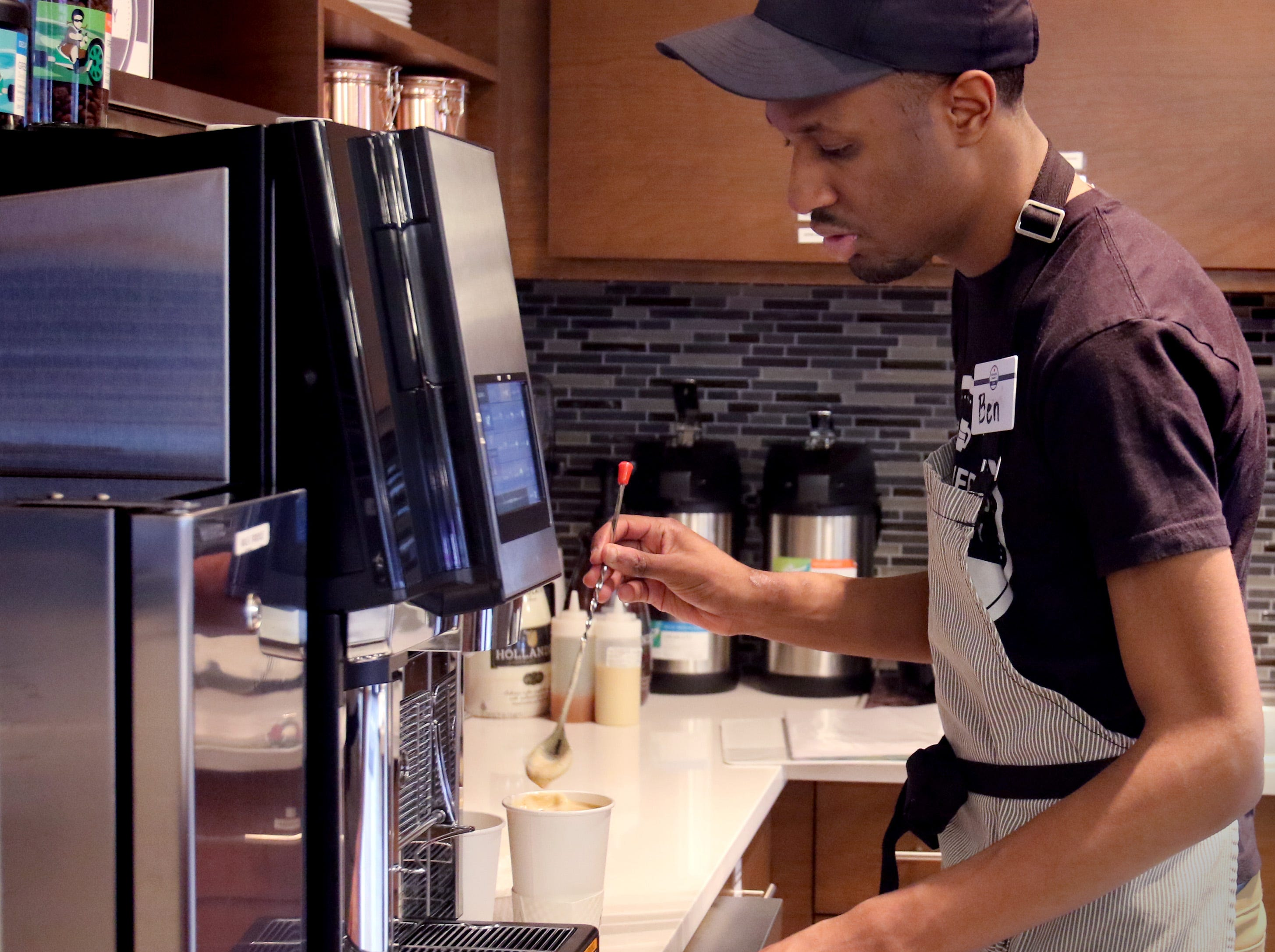 Ben Page mixes a customer's beverage at Shepherds Community Cafe inside Community State Bank in Union Grove on Dec. 20.