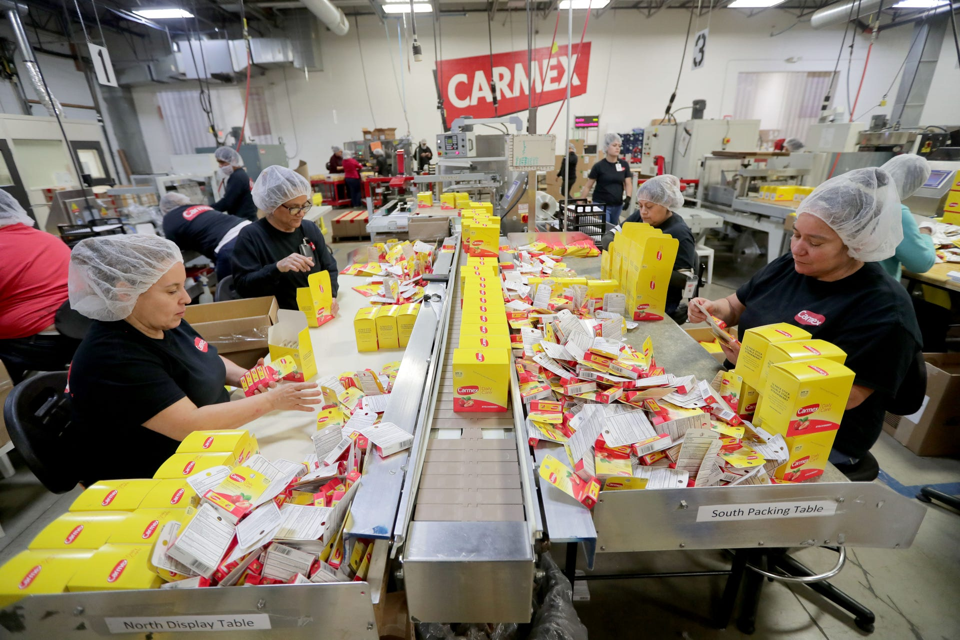 Employees work in the final packaging room at Carma Laboratories Inc., the maker of Carmex lip balm in Franklin.