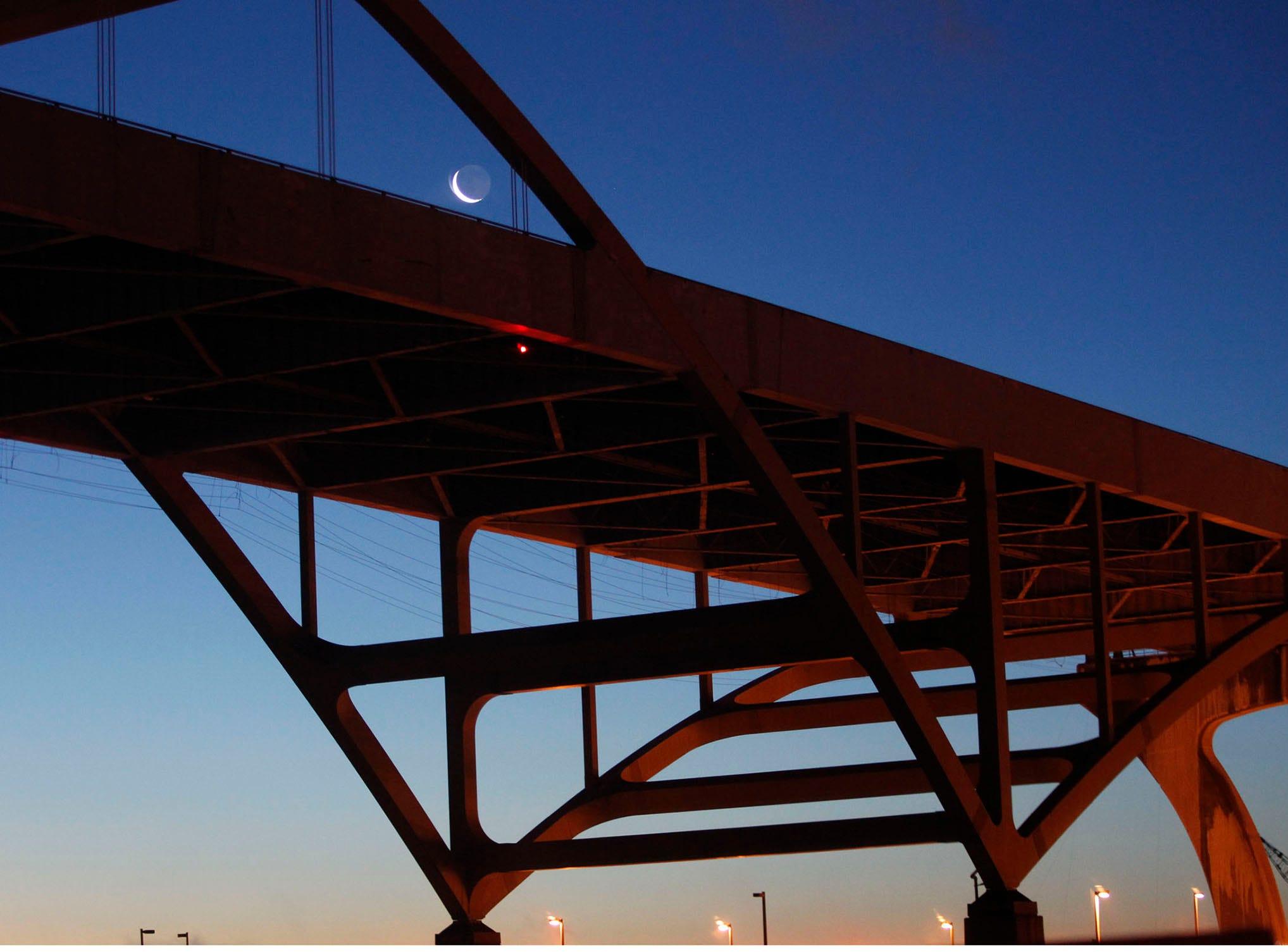 The moon is seen through the Hoan Bridge on Jan. 28, 2014.