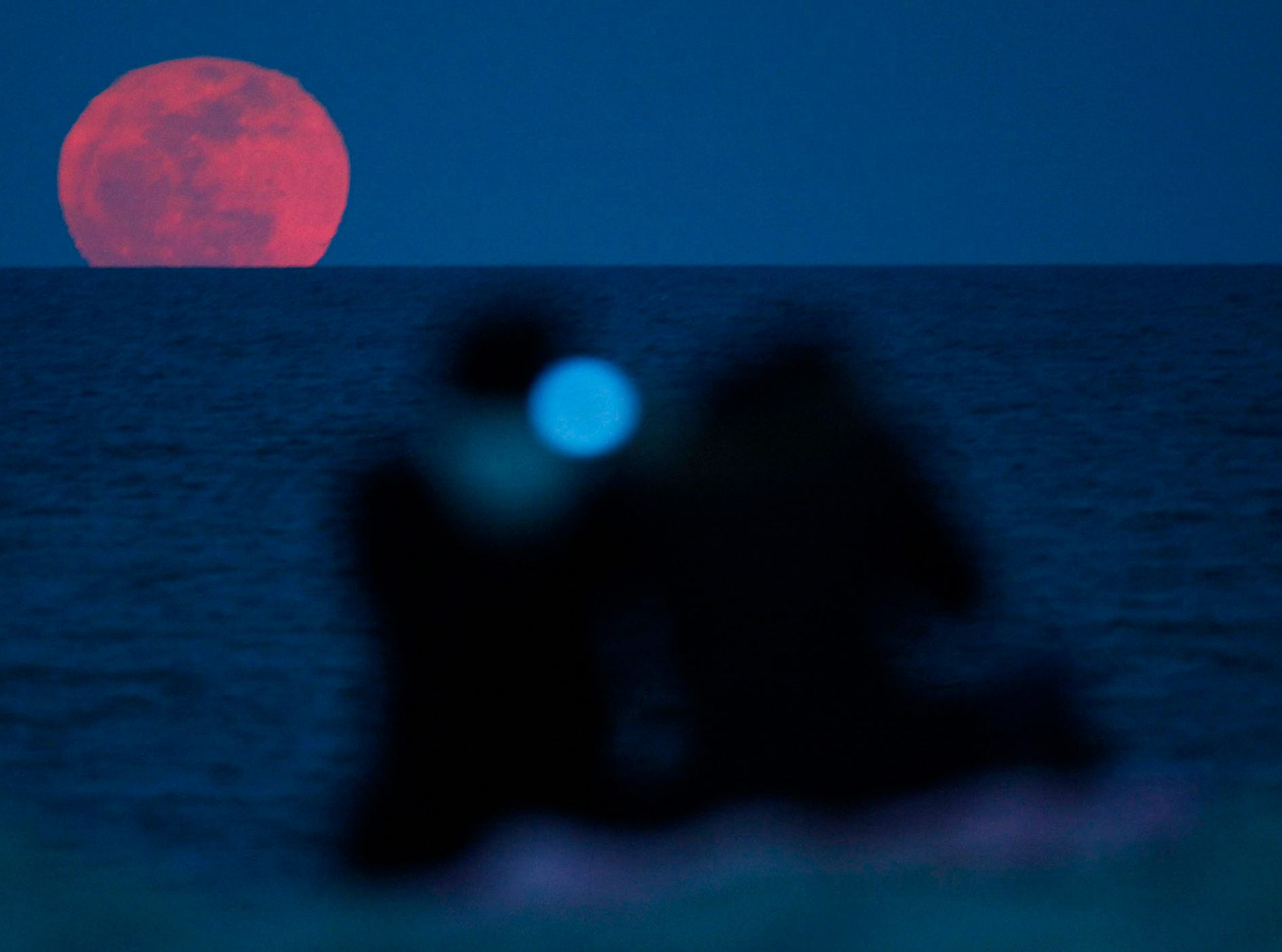 Josh Townsend and Ali Townsend of Milwaukee watch as the full moon rises over Lake Michigan near Bradford Beach March 19, 2011. The moon was closer to Earth than that it has been in more than 18 years.