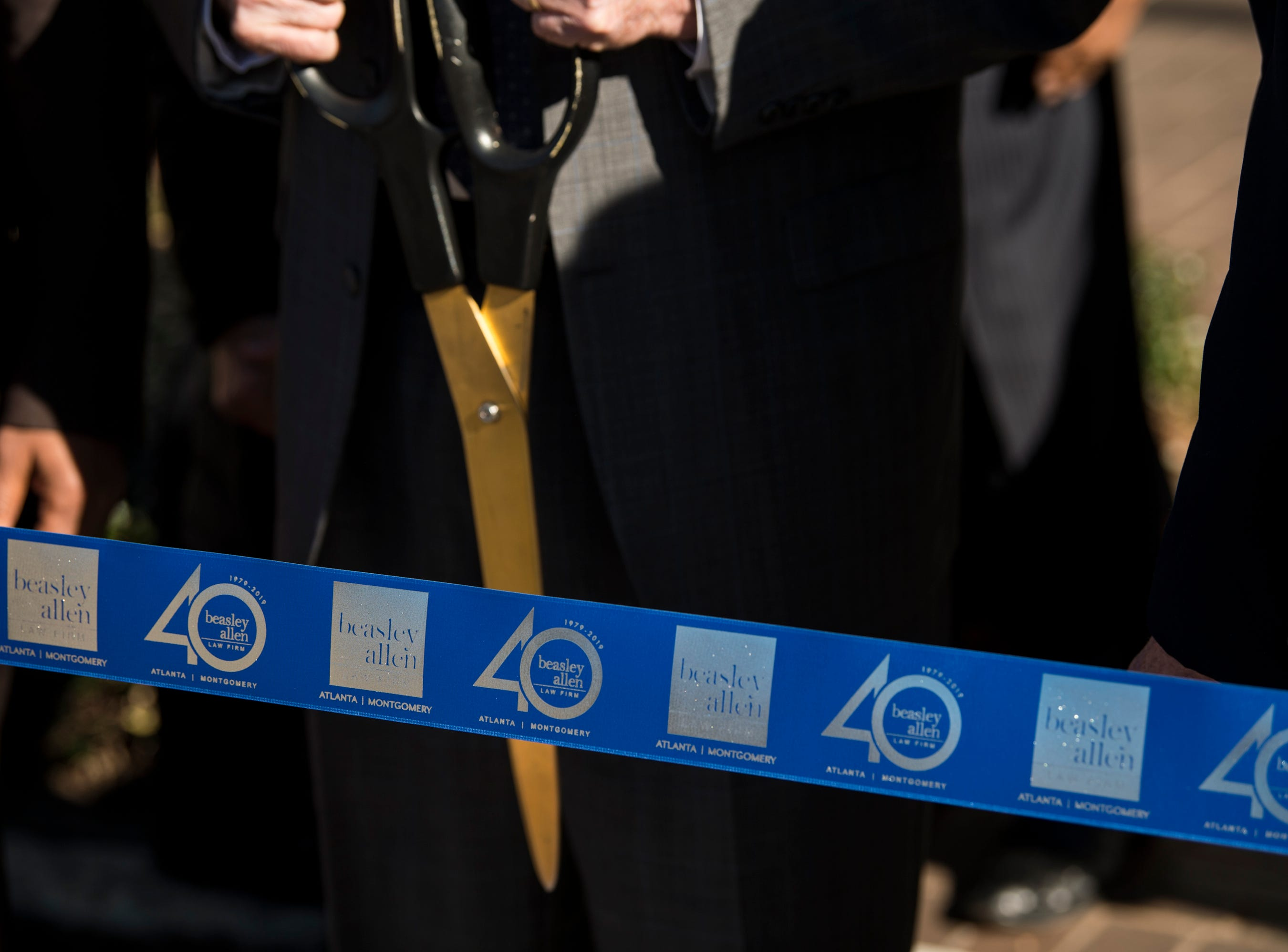 Ribbon is prepared to be cut during the Beasley Allen law firm 40th anniversary celebration in Montgomery, Ala., on Wednesday, Jan. 9, 2019.