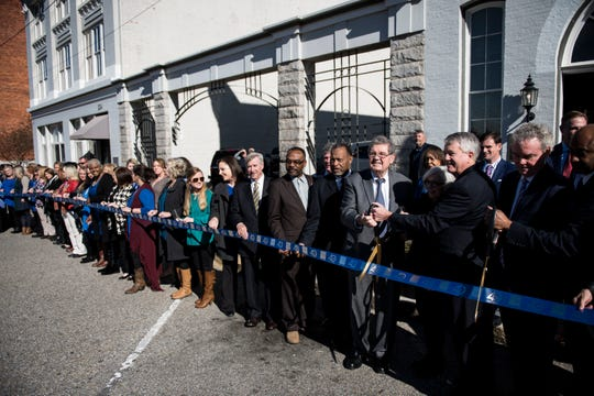 Members of the community cut a ribbon during the Beasley Allen law firm 40th anniversary celebration in Montgomery, Ala., on Wednesday, Jan. 9, 2019.