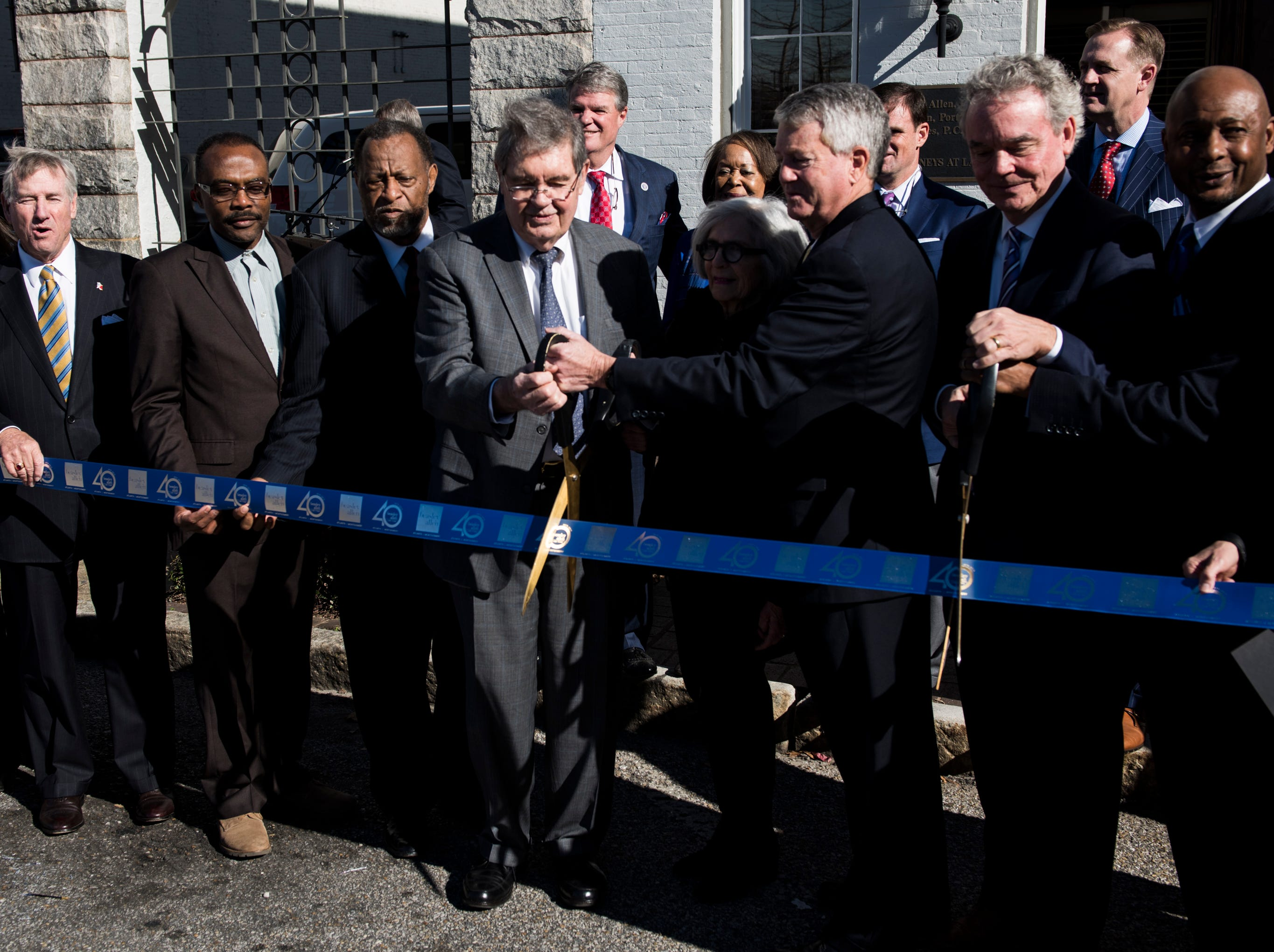 Jere Beasley, middle left, and Greg Allen, middle right, cut a ribbon during the Beasley Allen law firm 40th anniversary celebration in Montgomery, Ala., on Wednesday, Jan. 9, 2019.