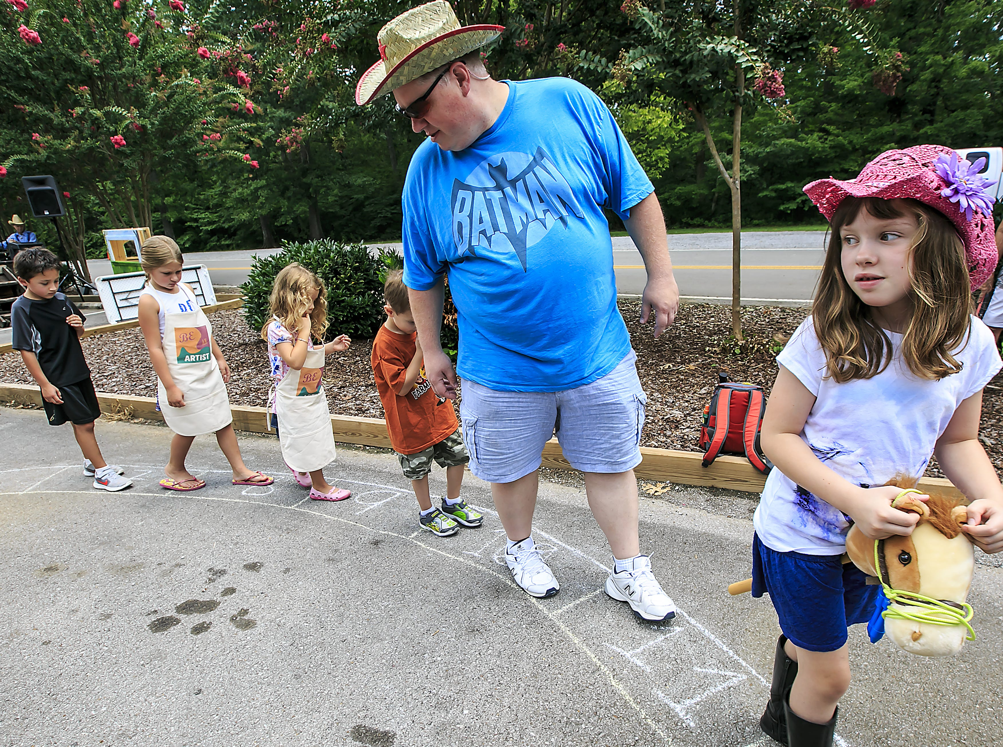 Gracie Sanders, right, is dressed for Wild Arts Day has she is followed by her father Keith and others during a T-shirt walk (similar to a cake walk) at Wild Arts Day at the Wilderness Station held at Barfield Crescent Park.