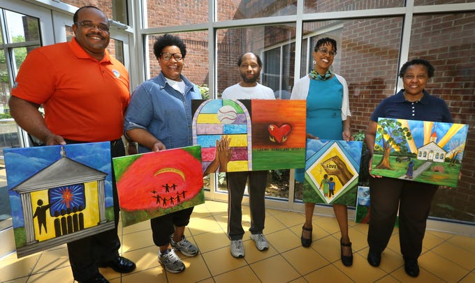 Ralph Buckingham, Mary Watkins, Leroy Hodges, Ifeoma Nwankwo, and Dr. Barbara Hodges hold art work created by participants from the Wisdom of the Elders program.