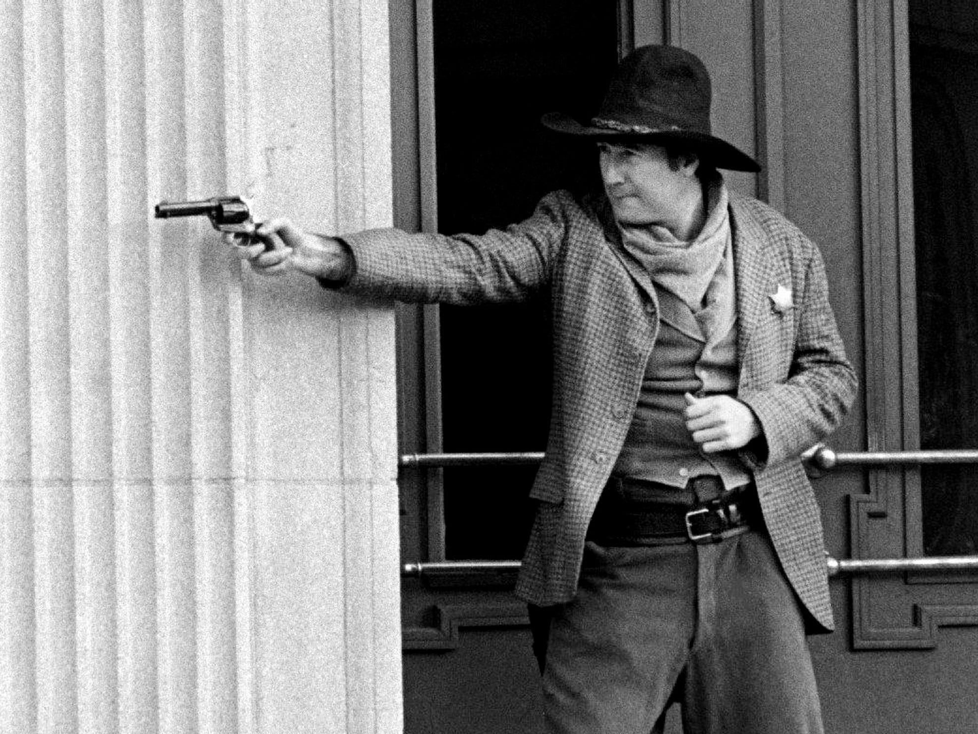 "Tennessean reporter-turned-deputy Ken Beck draws a bead on bank robbers from the doorway of the Robertson County Courthouse on Dec. 10, 1985. Johnny Cash and Kris Kristofferson, along with Beck, an extra for the day, were part of NBC Television's ""The Return of Frank and Jesse James,"" being filmed in Springfield."