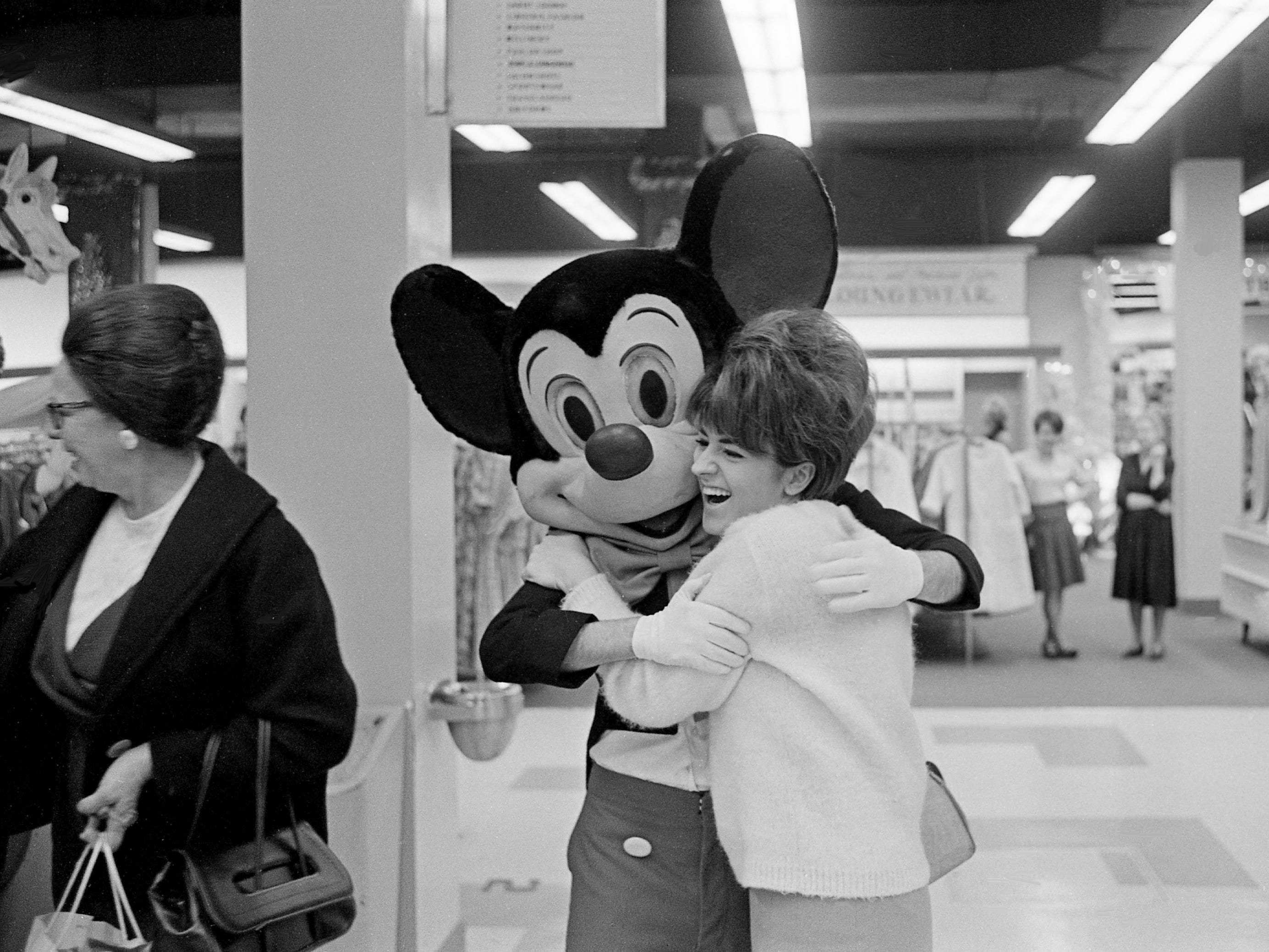 Mickey Mouse surprises a Christmas shopper with a big bear hug at Harveys downtown department store Dec. 9, 1965. Playing Mickey for the day and story is Tennessean reporter William Greenburg.