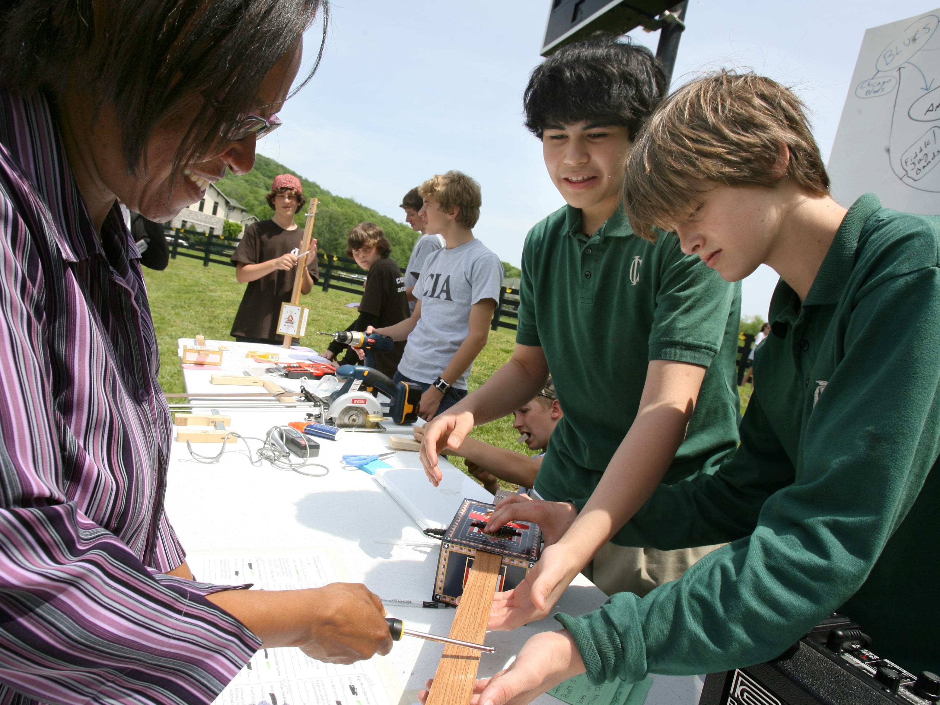 Parent Cathy Moulton checks out a cigar box slide guitar made by Kevin Moran, center, and Louis Dunn, right, at Currey Ingram Academy after the duck race in Beech Creek next to the school on May 7, 2008.