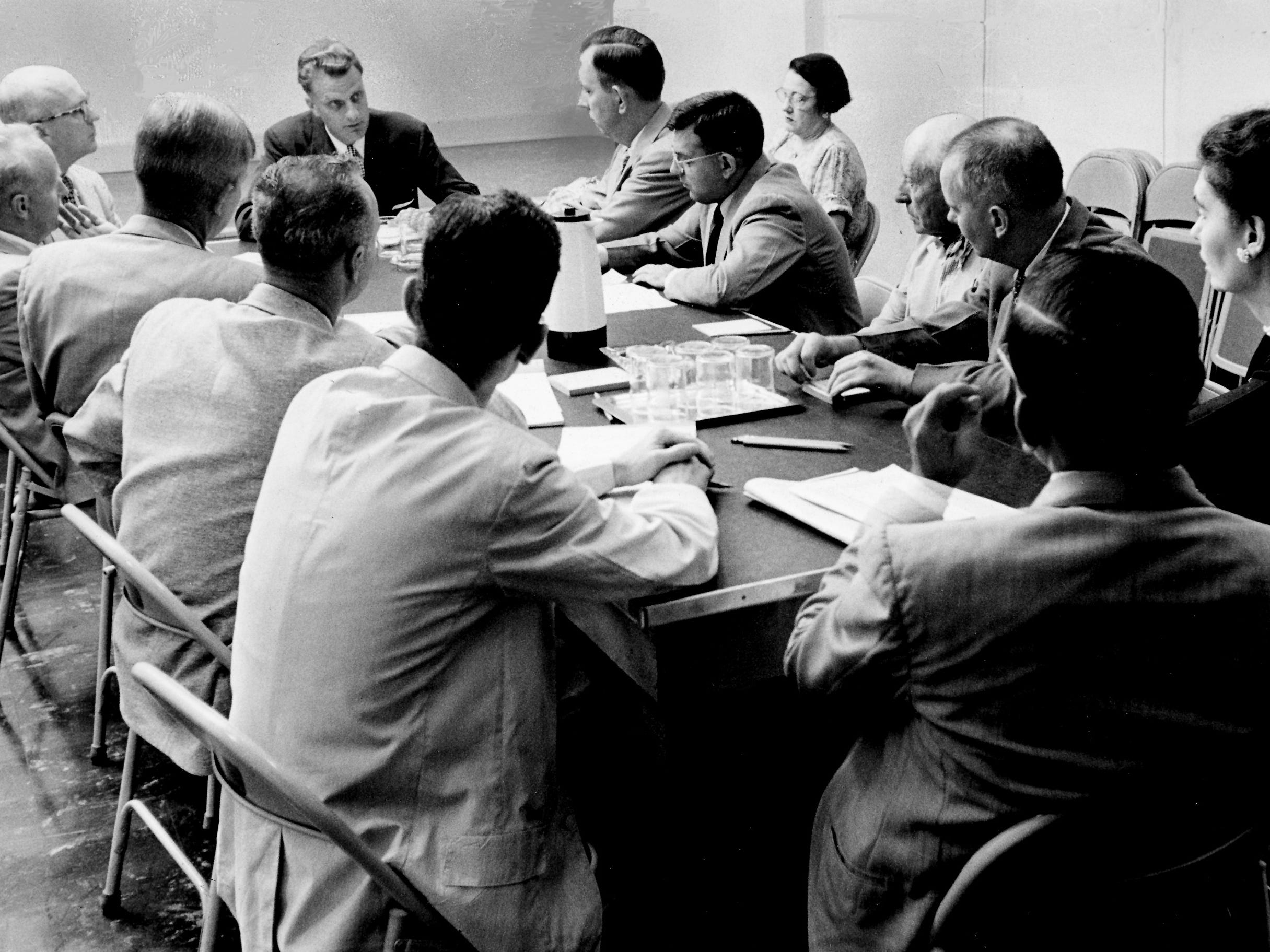 Around the The Tennessean's conference table, journalists fired questions Sept. 11, 1954, at the Rev. Billy Graham, at the head of the table, ranging from world events to his own background. Members of The Tennessean, from Graham's left clockwise, are: Hugh Walker, stenographer Beatrice Commander, James Carty, Lindsay Glegg, Wayne Whitt, Louise Davis, Creed Black, Charles Daw, Ed Freeman, Nat Caldwell, Dr. Alan Redpath and Coleman A. Harwell.