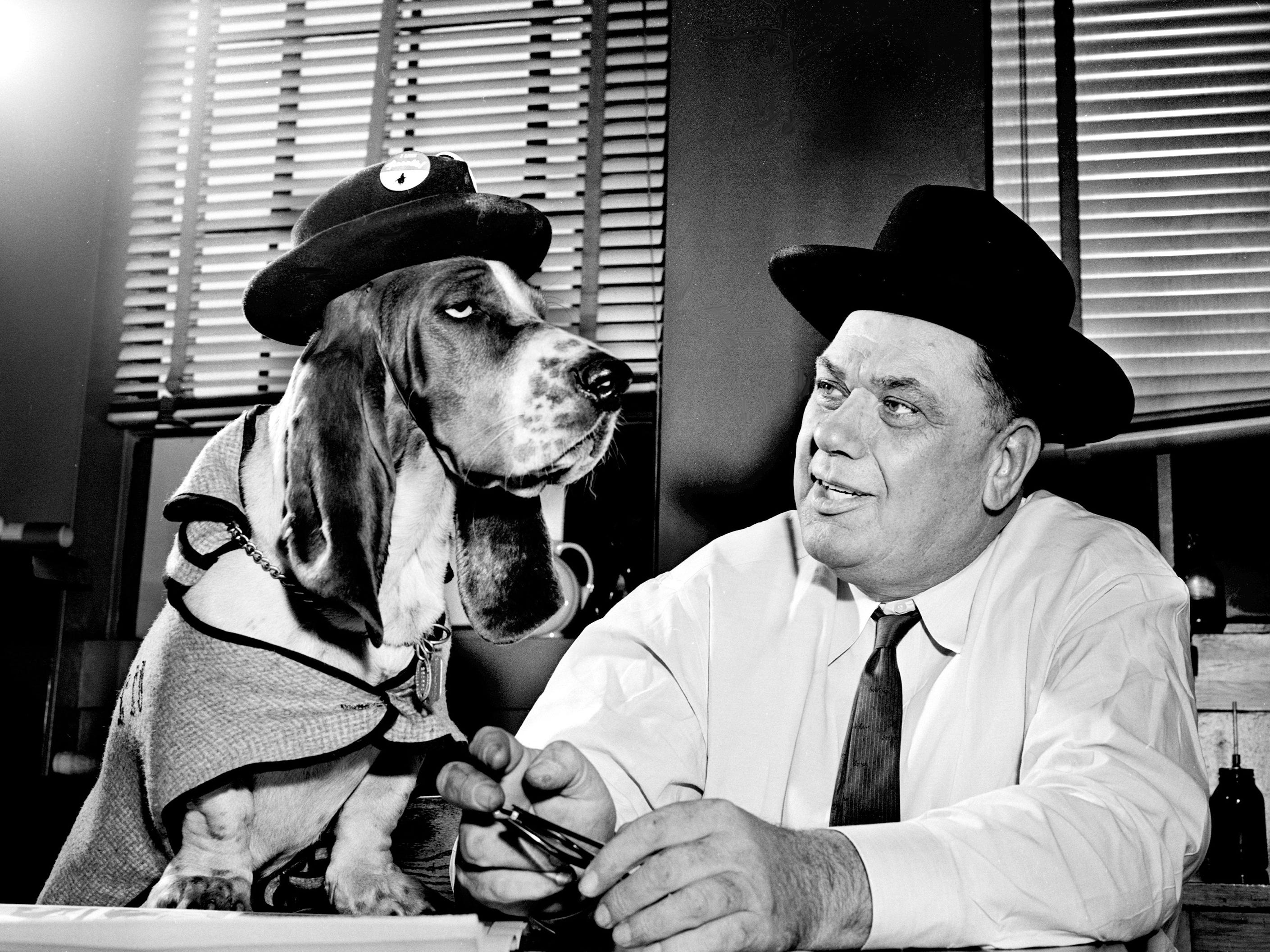 Tennessean reporter and columnist Elmer Hinton shares a moment with a basset hound in the city newsroom Nov. 22, 1960.