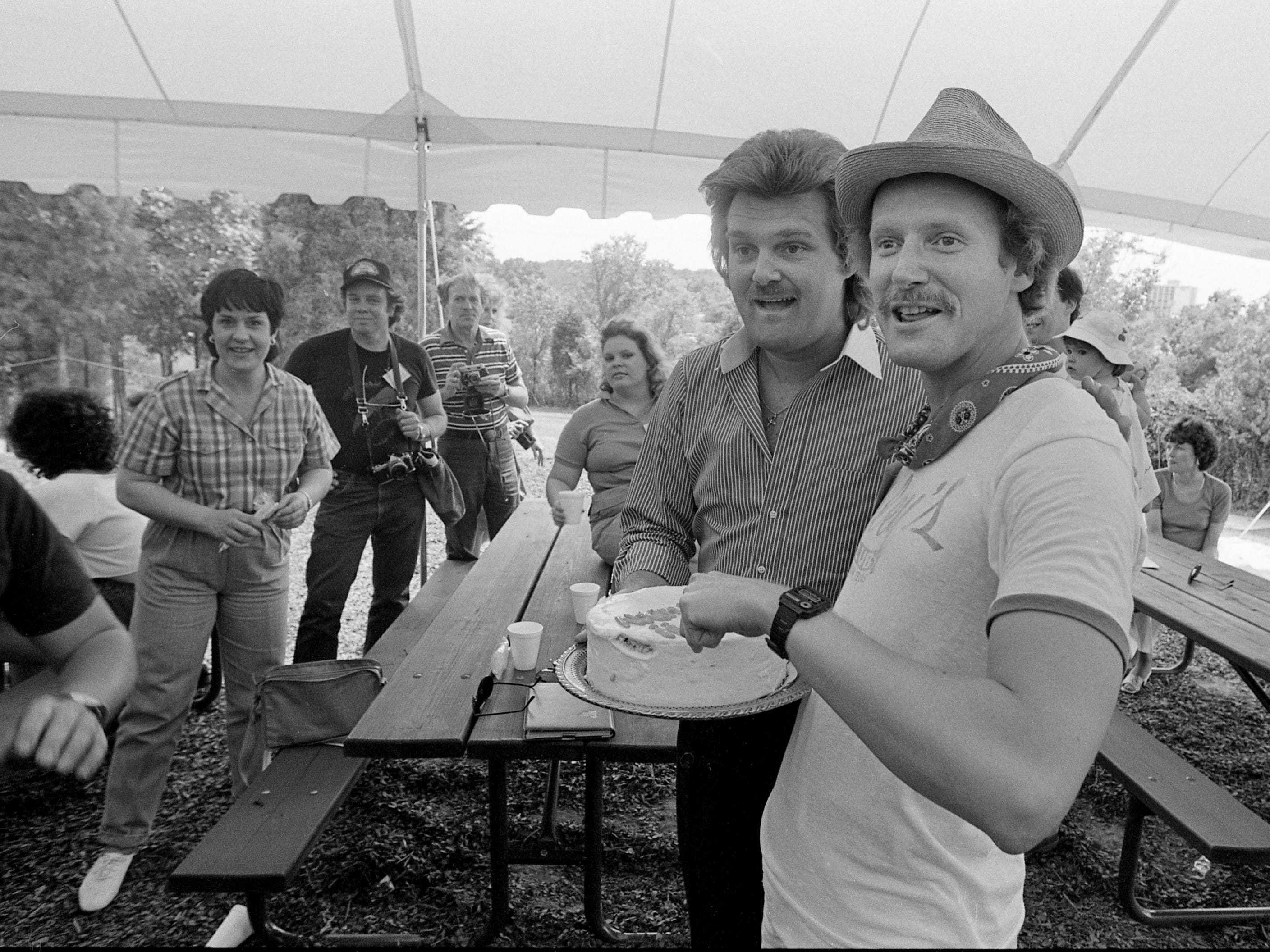 Ricky Skaggs, center, poses with Tennessean music reporter Robert K. Oermann, right, who brought a cake to Skaggs' private picnic and show for his fan club members June 6, 1984, during Fan Fair.