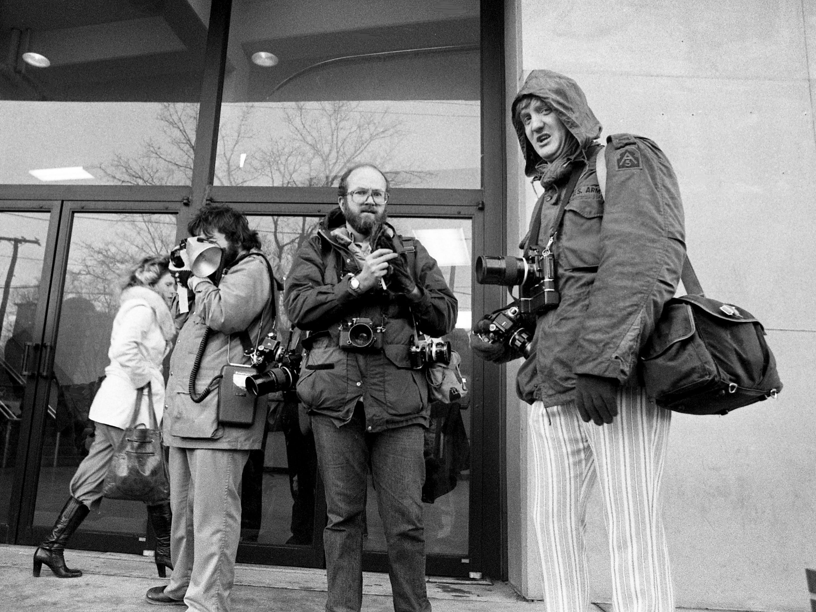 Tennessean photographers Bill Welch, center, and Dan Loftin, right, watch protesters of the Davis Cup match between the U.S. and South Africa at Vanderbilt University's Memorial Gym on March 17, 1978.