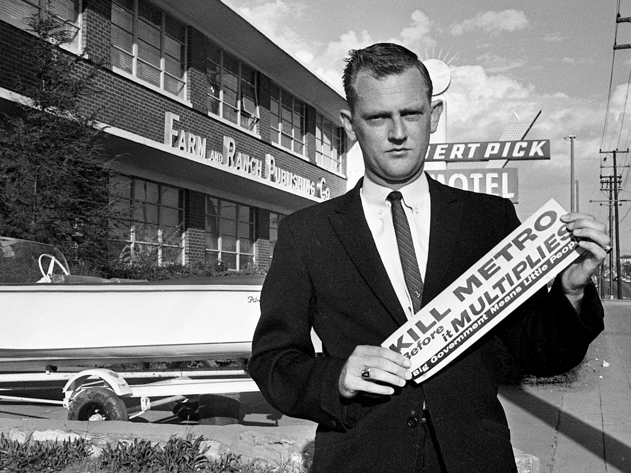 "Rudy Abramson, reporter for The Nashville Tennessean, holds a ""Kill Metro"" bumper sticker given to him at Farm and Ranch Publishing Co. on May 3, 1962. Opponents of Nashville-Davidson County consolidated government, including elements of the ultra conservative John Birch Society, have started an early campaign against it with bumper stickers."