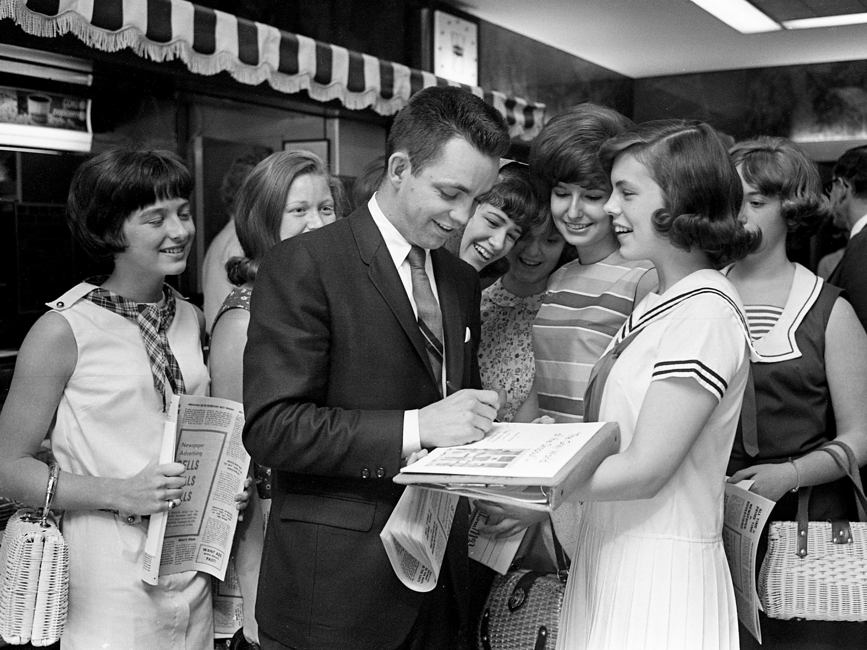"Frank Ritter, center, reporter for The Tennessean, autographs a booklet, ""The Gray World of the Dropout,"" for Betty Billingsley, a Lipscomb High School student, after the world premiere of the movie ""Did You Hear What I Said?"" at the Crescent Theater on May 21, 1966. Ritter starred in the film, based on an assignment that also produced the booklet."