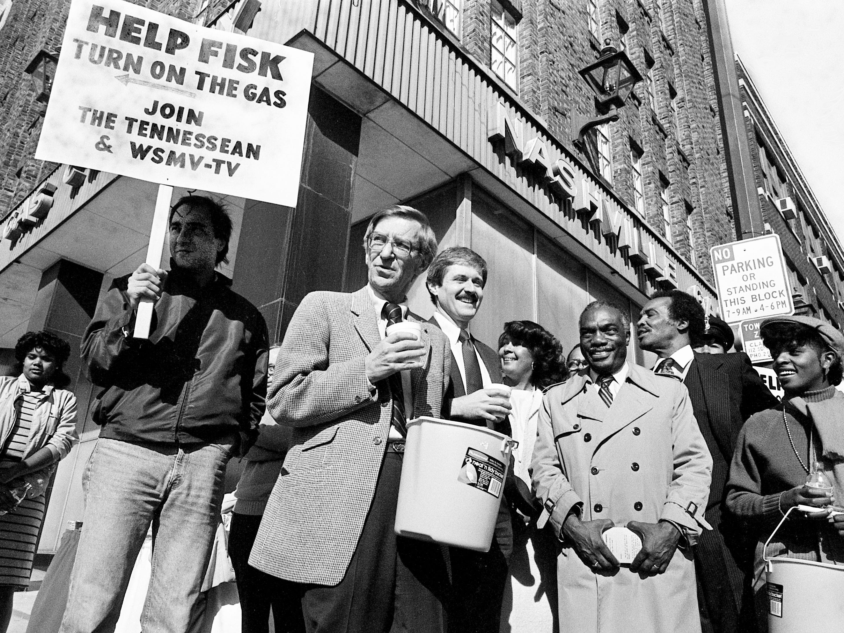 "The fundraising drive to ""turn on the gas"" at Fisk University brought people from a variety of occupations to the Nashville Gas Co. offices Nov. 13, 1983. Among them are Randy Hilman, left, a Tennessean reporter who holds a sign seeking contributions from passing motorists; Lloyd Armour, executive editor of The Tennessean; Mike Kettenring, president and general manager of WSMV; Walter Leonard, president of Fisk; Walter Hunt, an aide to 5th District Rep. Bill Boner; and Mearl Purvis, director of community affairs for WSMV."