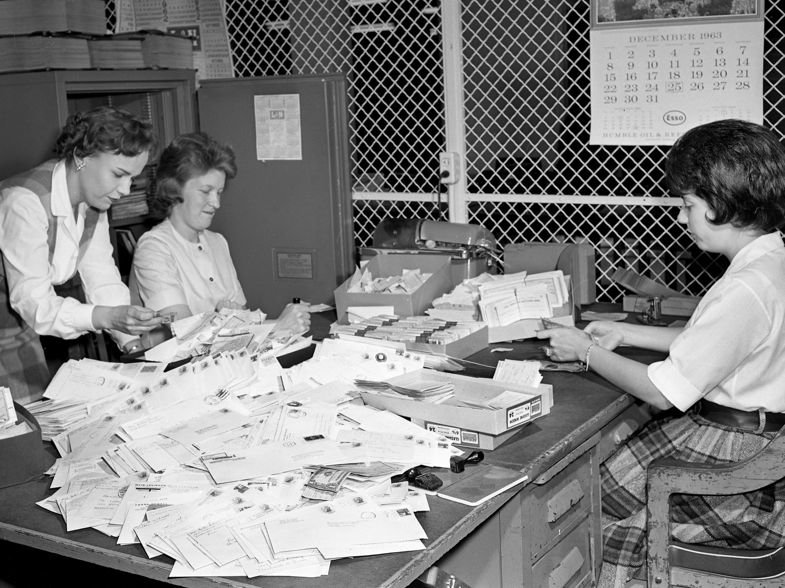 "This is only a portion of the thousands of orders already placed for The Nashville Tennessean's new booklet, ""He Gave His Live,"" which deals with the assassination of President John F. Kennedy. Sorting the orders Dec. 12, 1963, are Shirley Hewitt, left, associate promotion director for The Tennessean, and Florence White and Barbara Flippin, both employed by the bookkeeping department of the Newspaper Printing Corp."