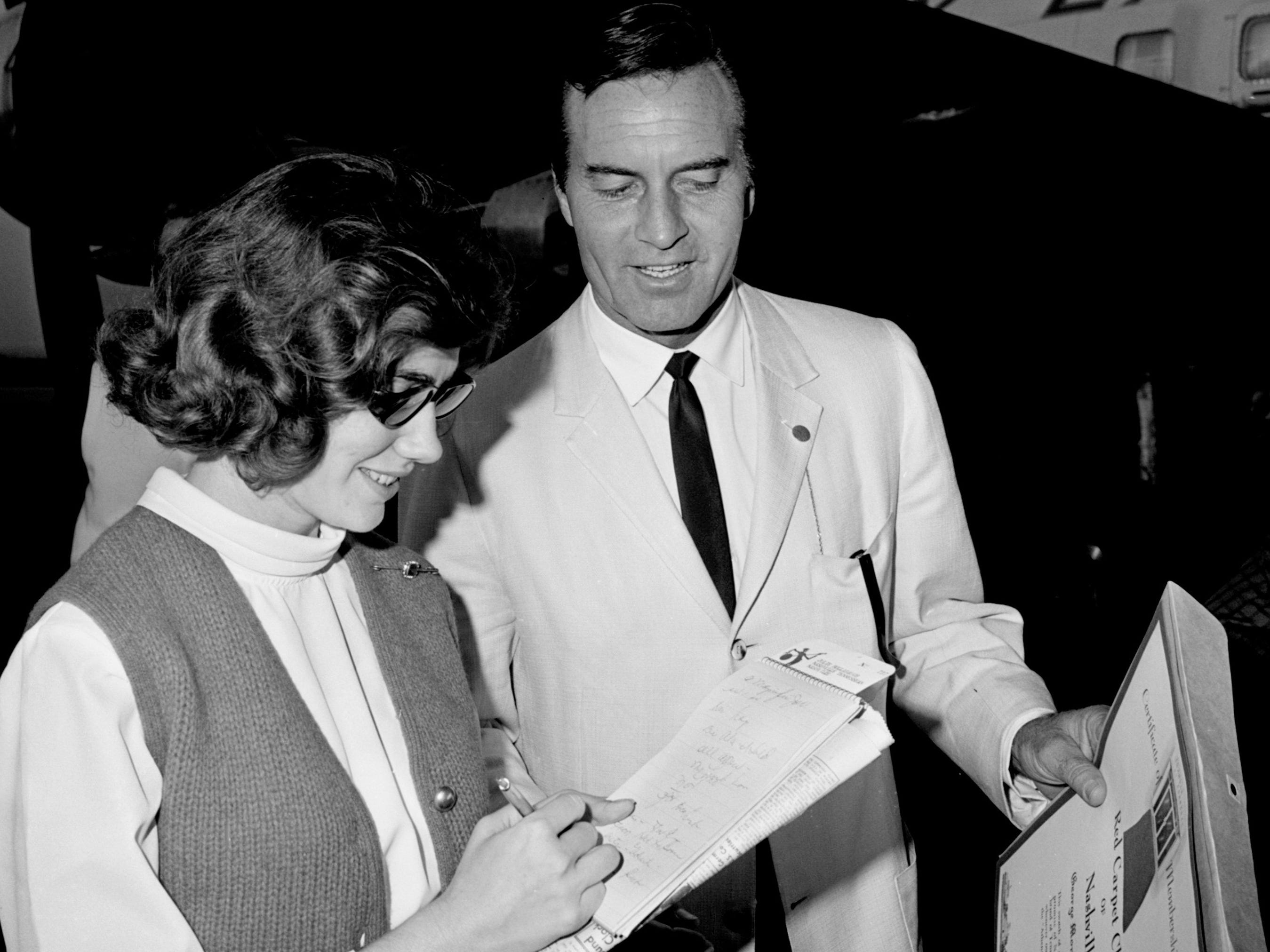 "Tennessean reporter Julie Hollabaugh, left, interviews actor George Montgomery, who just arrived here Nov. 5, 1964, for the showing of ""Your Cheatin' Heart,"" the film biography of Hank Williams Sr."
