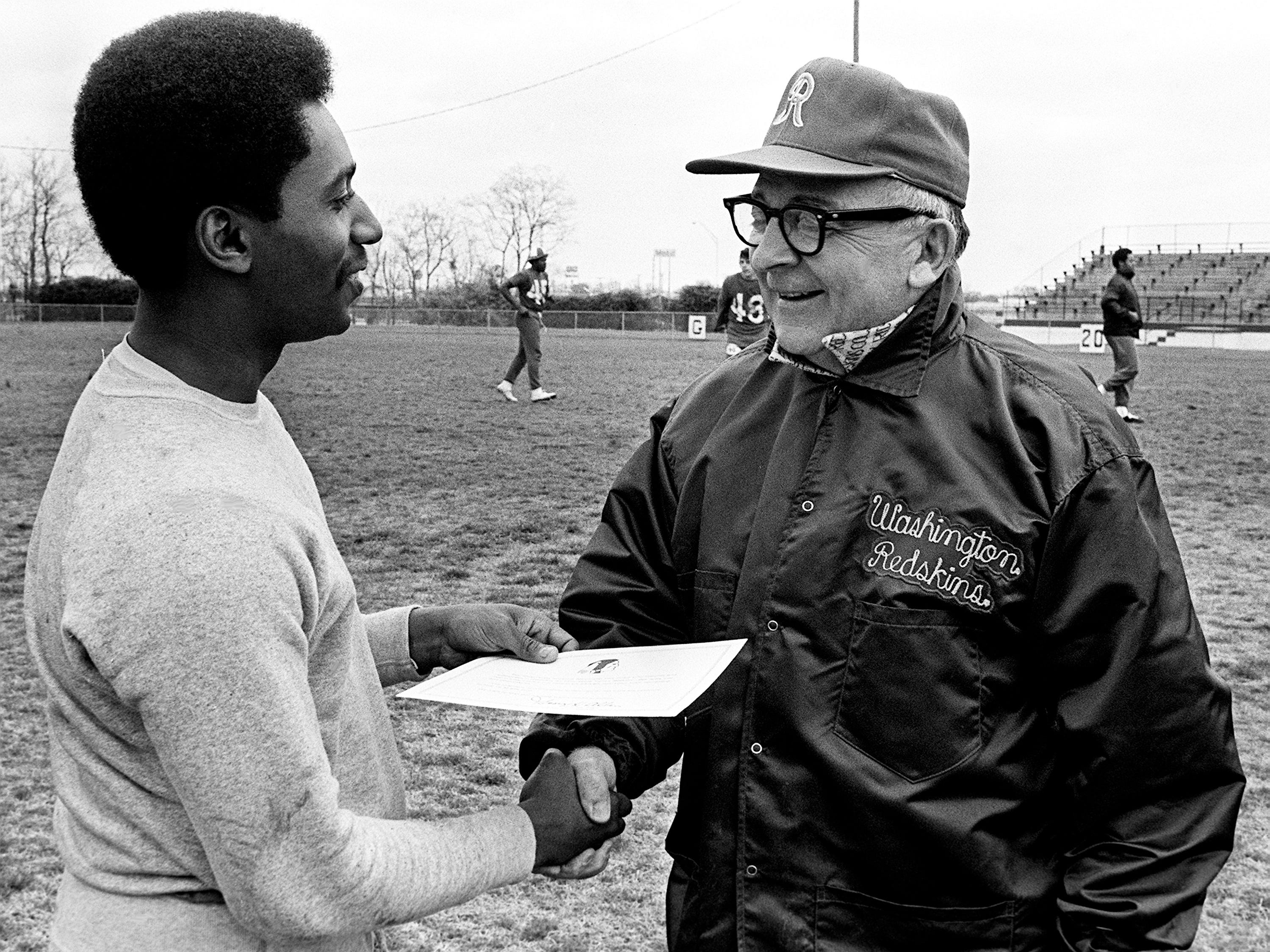 Washington Redskins player personnel director Tim Temerario, right, shakes hands with Tennessean reporter Dwight Lewis, who appeared at Overton High School on March 16, 1974, to participate in the free agent tryout camp sponsored by the Redskins. Lewis also was presented with a certificate saying he does not have the potential to help the Redskins at this time.