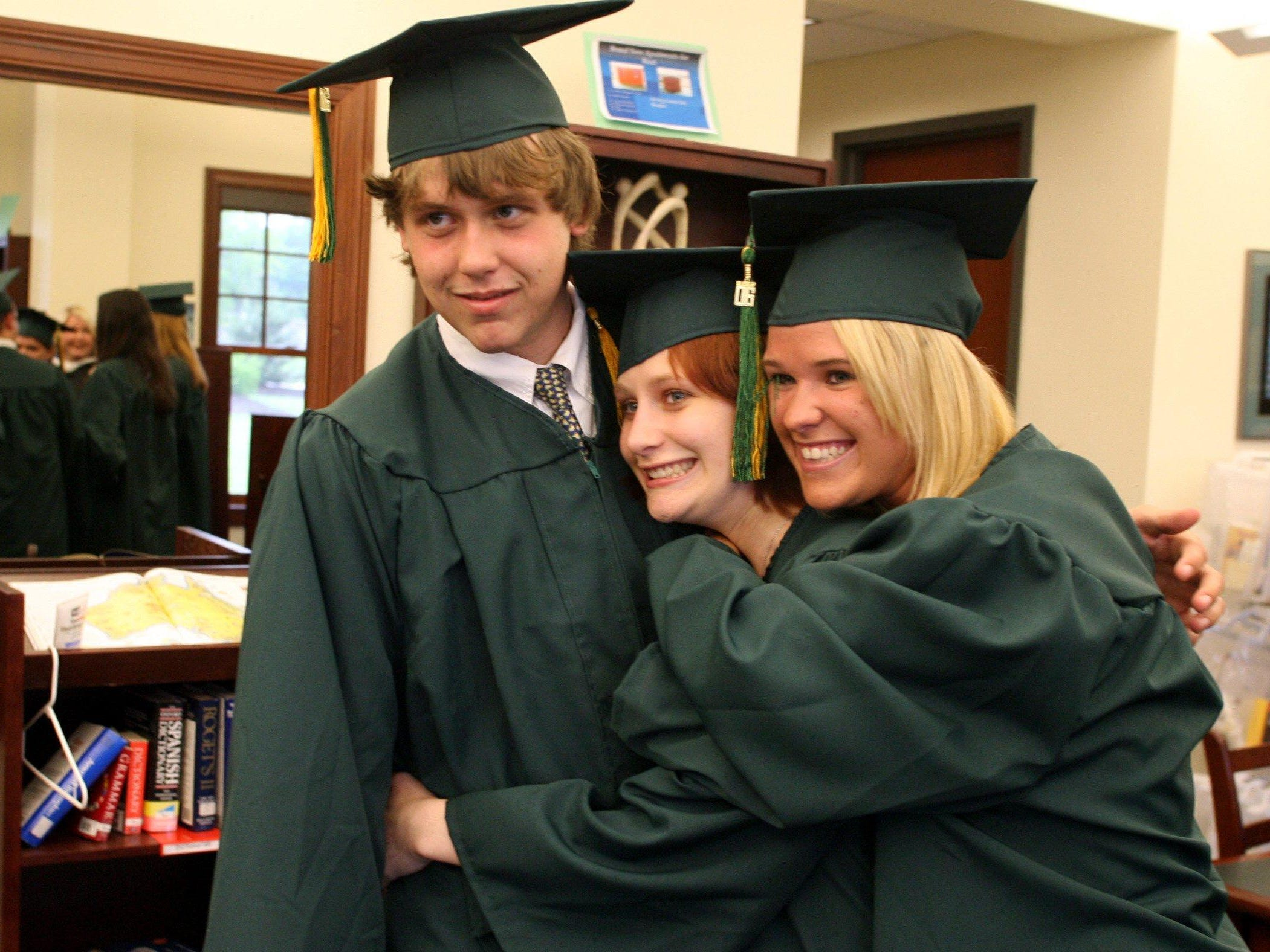 Robertson Andrews, Heather Thompson and Joy Ash embrace as students prepare to graduate at Currey Ingram Academy in 2006.