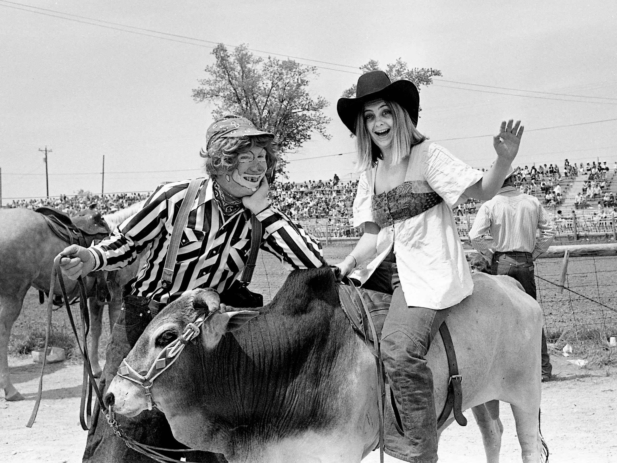 Tennessean cowgirl and reporter Kathleen Gallagher, right, hams it up with Andy Shipp, of Athens, Ala., who follows the rodeo circuit with his trick baby Brahman bull, Ajax. They were working at the 24th annual Rotary Club Franklin Rodeo on May 5, 1973.