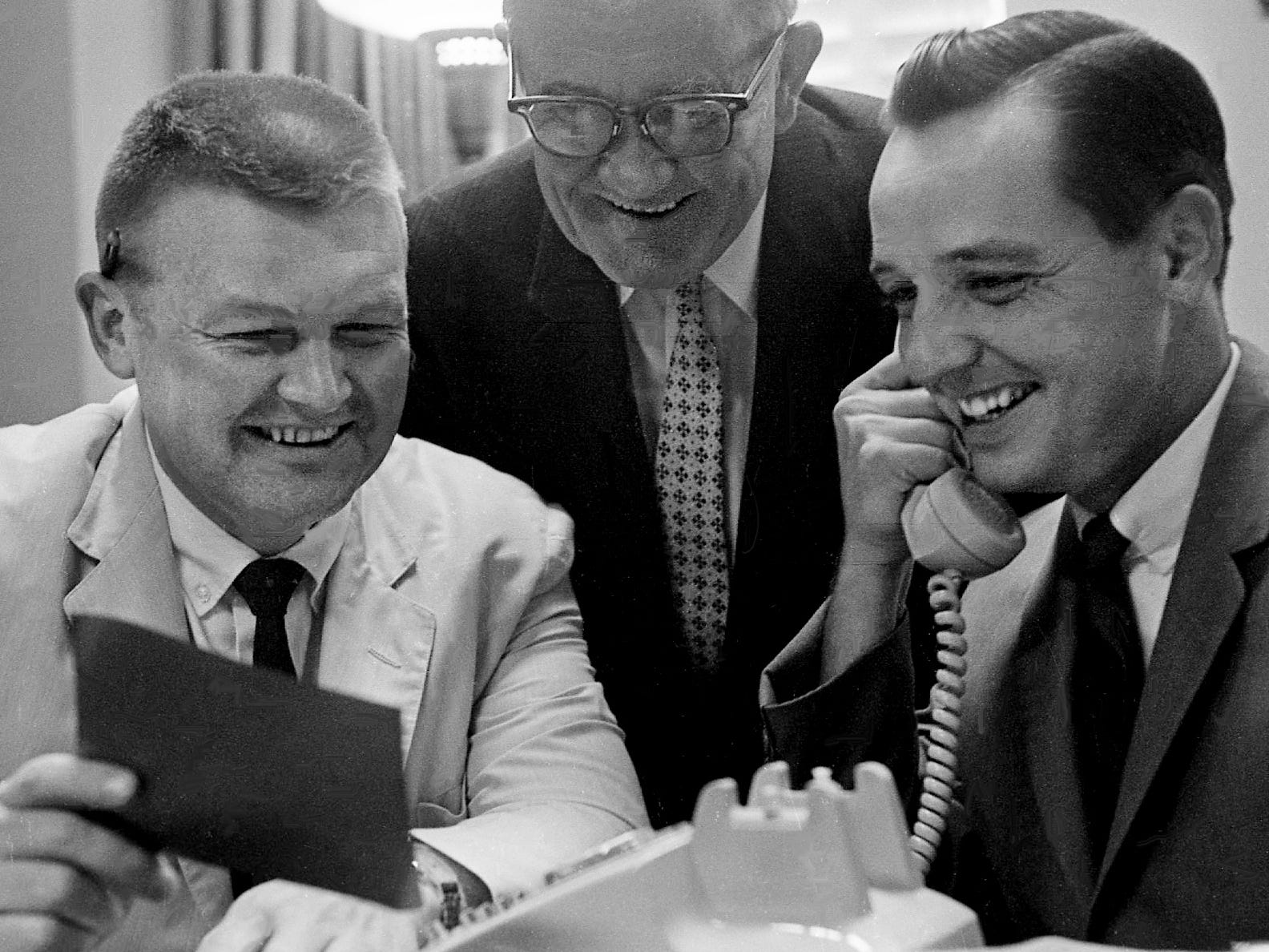 Tennessean editorial writer Gene Graham, left, reads the news of his and veteran reporter Nat Caldwell's Pulitzer Prize win as publisher Amon Carter Evans, right, talks with Caldwell by phone May 7, 1962. Caldwell was on an assignment in Texas. Between them is editorial cartoonist Tom Little, who won a Pulitzer Prize for his work in 1957.