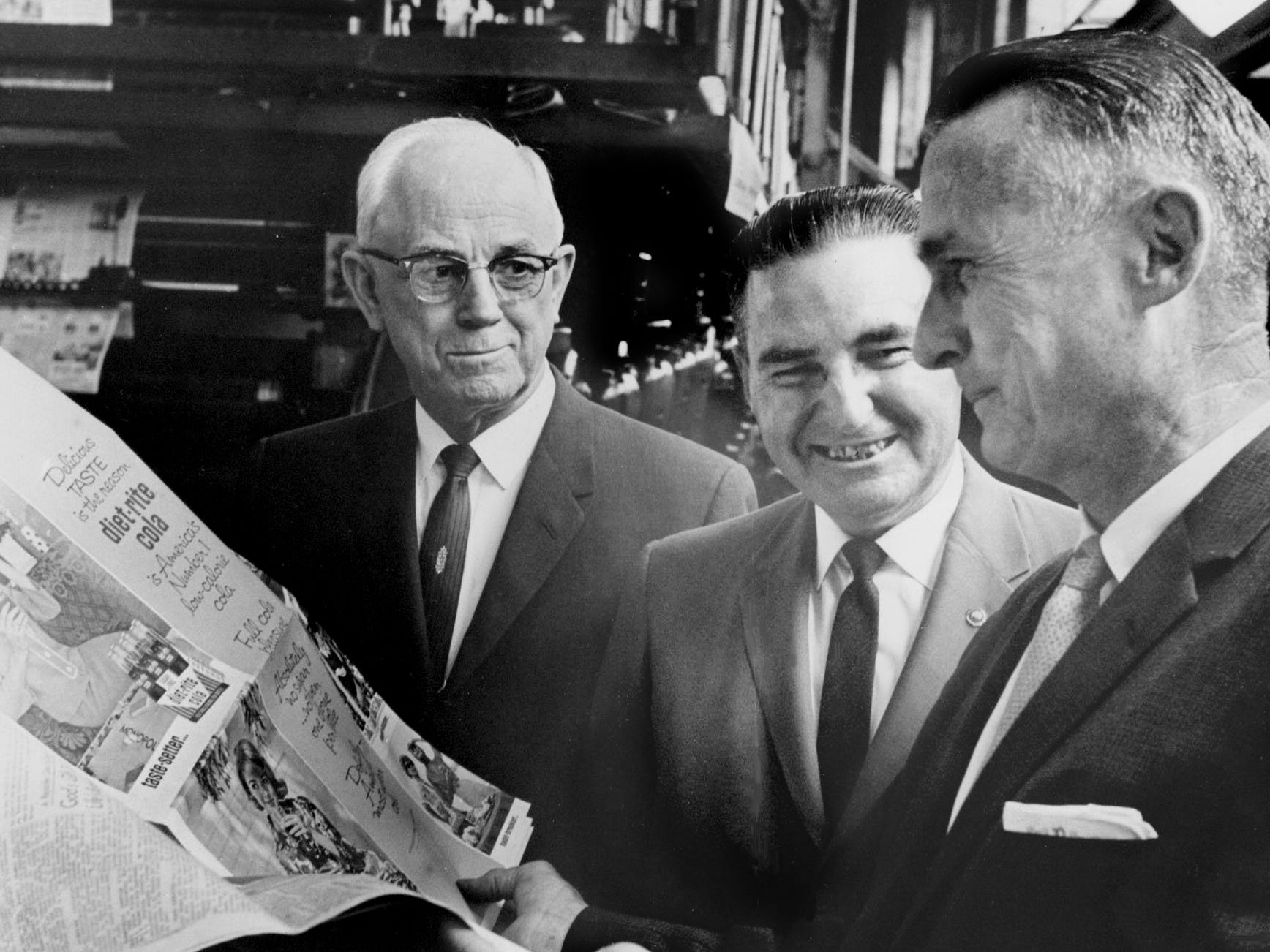 "Cletis E. Luther, left, president, Royal Crown Bottling Co.; Fred McWhorter, production manager, Newspaper Printing Corp.; and Ed Edmondson, general advertising manager, NPC, survey the historic first run of an ad in the new ""SpectaColor"" rotogravure process, bringing magazinelike reproduction quality to newspapers, on May 26, 1962."