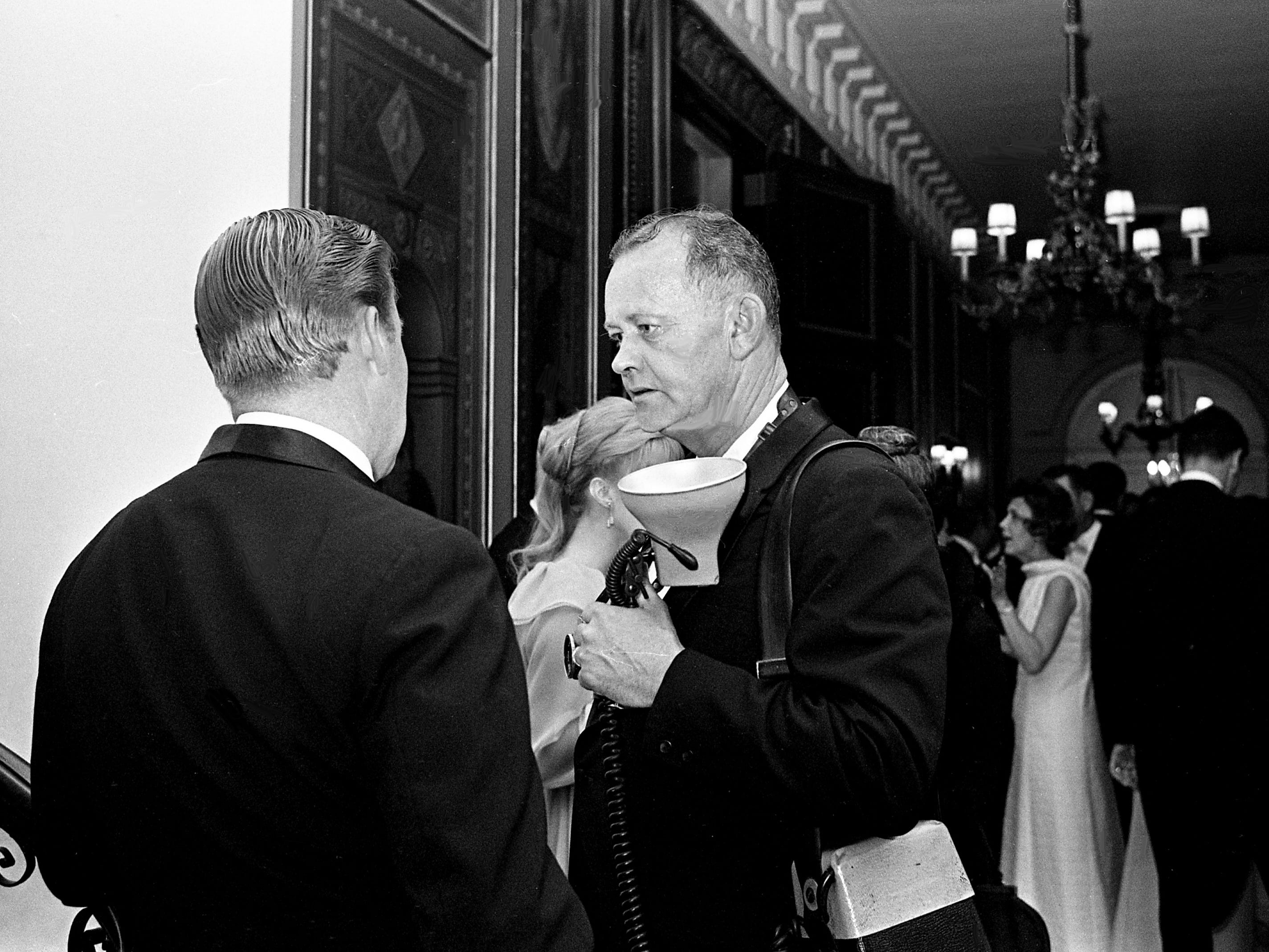 Tennessean staff photographer Bill Preston, right, talks with one of the guests during the Swan Ball on June 8, 1968. Preston was one of four photographers covering the event for the paper.