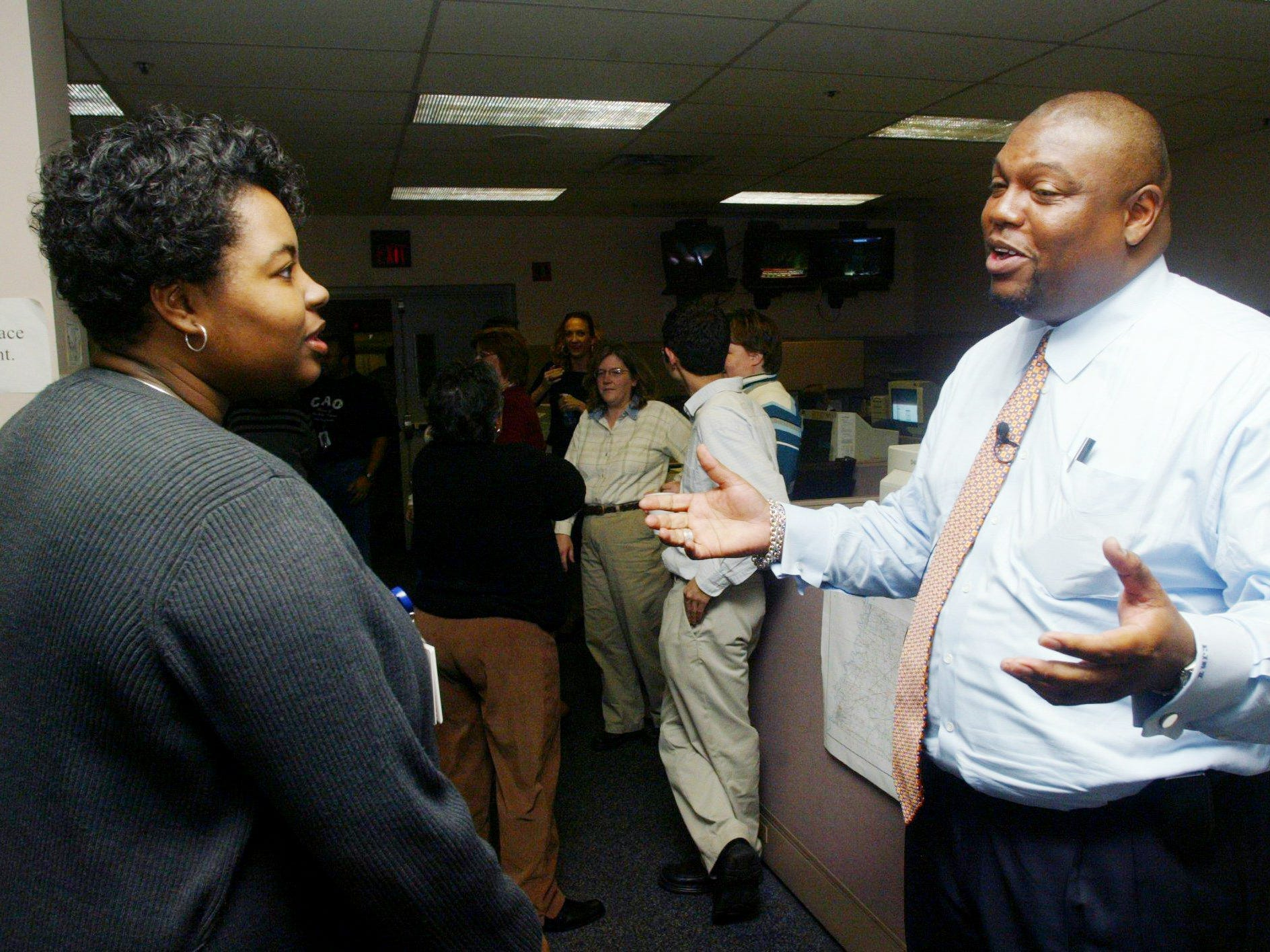 Everett J. Mitchell II, right, who was named vice president of news and editor of The Tennessean, talks with reporter Michelle Shaw after speaking to the staff in the newsroom Dec. 6, 2004.