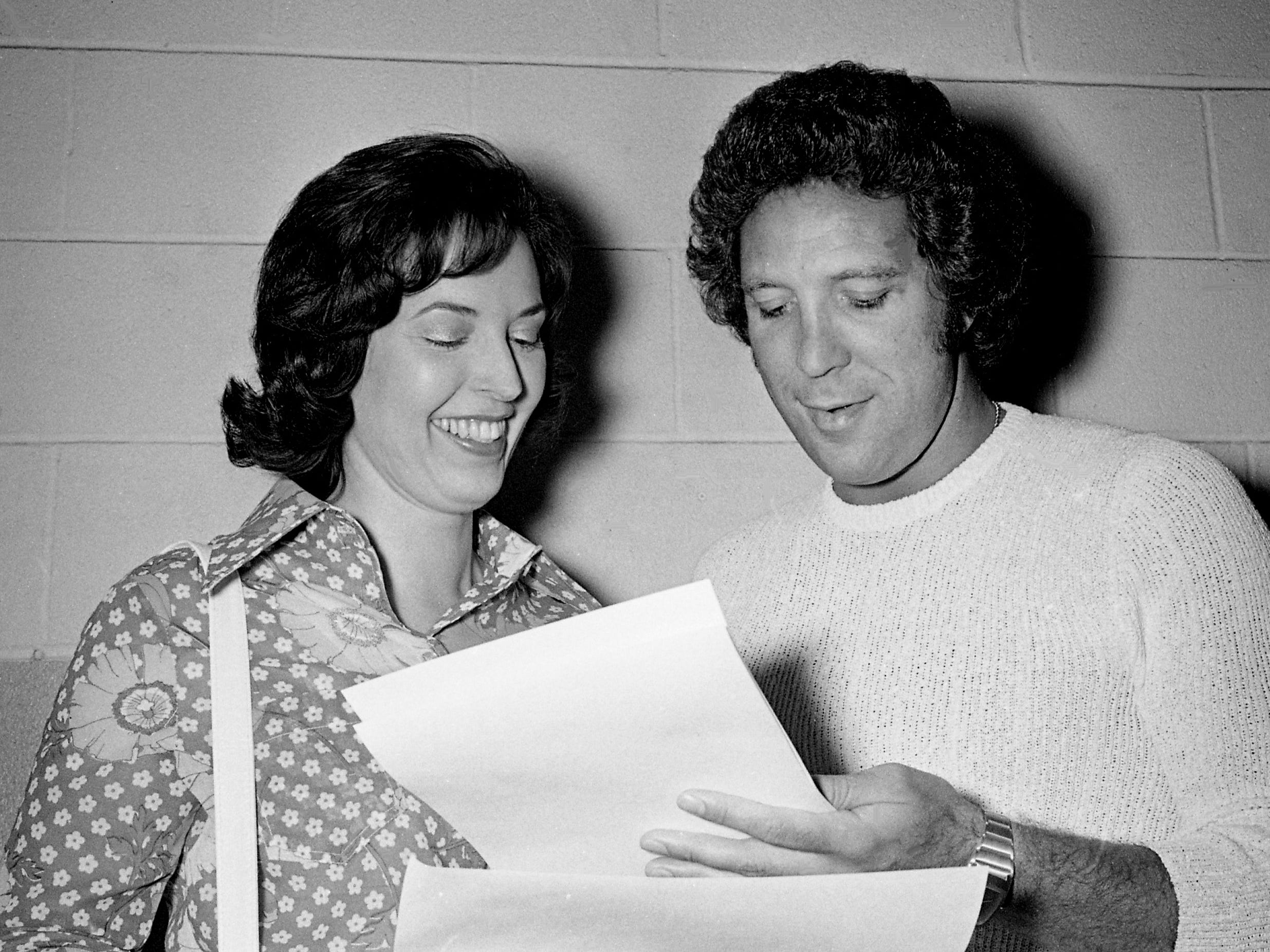 Singer Tom Jones, right, before his concert May 18, 1973, at Municipal Auditorium, signs photographs for Connie Craighead, 23, who lies paralyzed in Madison Hospital. Pat Swingley, left, the Tennessean reporter who wrote about Craighead's fondness for the singing idol, will deliver the photos to Craighead.