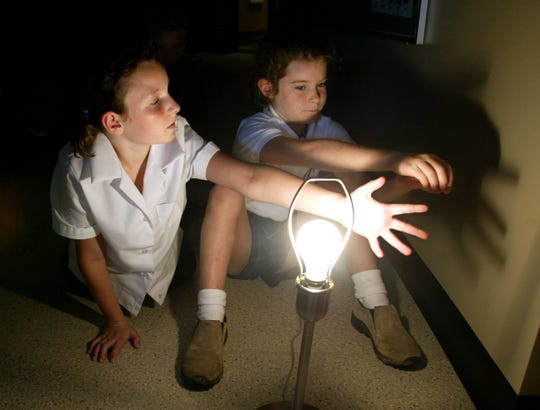 """Arabella Everly, 9, and Ann Winston Thym make shadow puppets on the wall as they learn the phases of the moon in the """"discovery"""" lab at Currey Ingram Academy in Brentwood in 2003."""