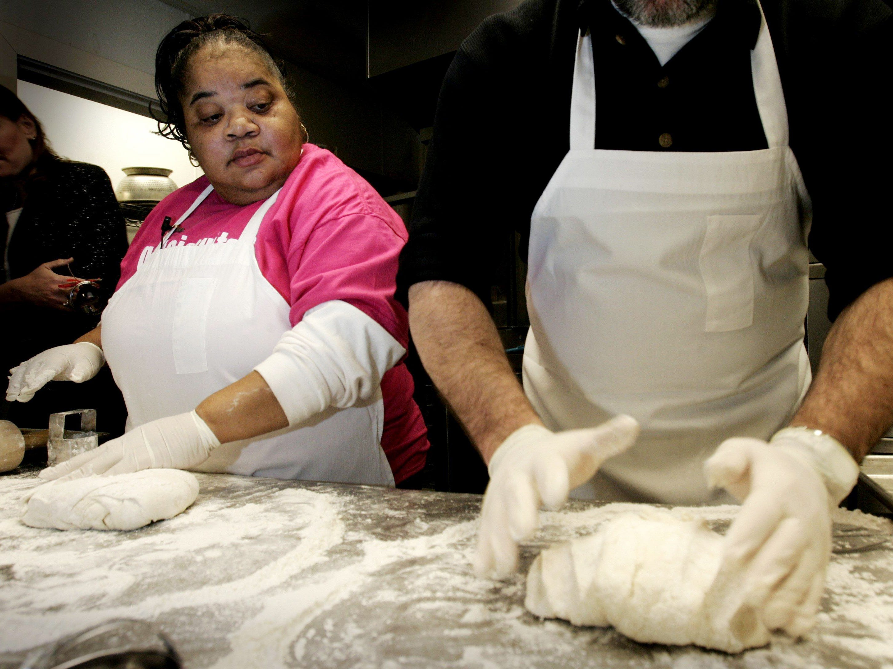 Carol Fay, left, the Biscuit Lady at Loveless Cafe, watches Tennessean reporter Jim Myers make his biscuit dough in the kitchen at Loveless on Jan. 30, 2007. The two had a bake-off for the best biscuits.