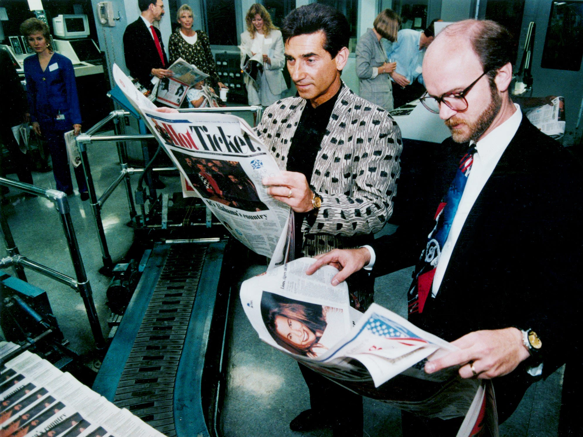 Richard Sterban, left, singer with the Oak Ridge Boys, and Mike Christopher, The Tennessean's assistant to the president, check out the first copies of Hot Ticket, a new publication designed for tourists, as papers come off the press May 6, 1994.