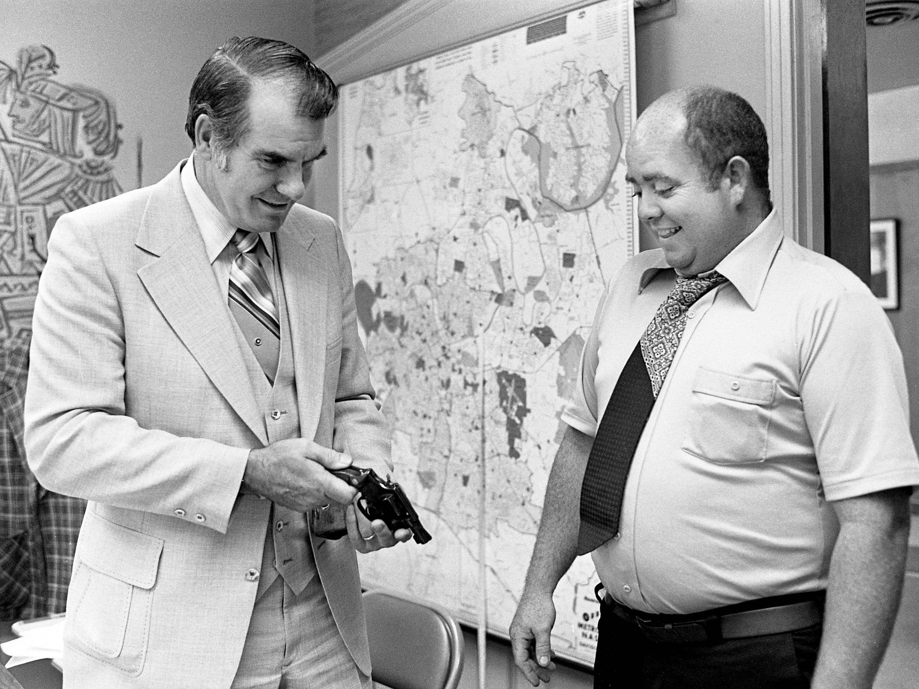 Metro Police Chief Joe Casey, left, is reunited May 24, 1977, with his service revolver that was stolen along with his car more than a year ago. Tennessean reporter Jerry Thompson, right, was given the pistol by a new source who asked that the pistol be returned to the chief.