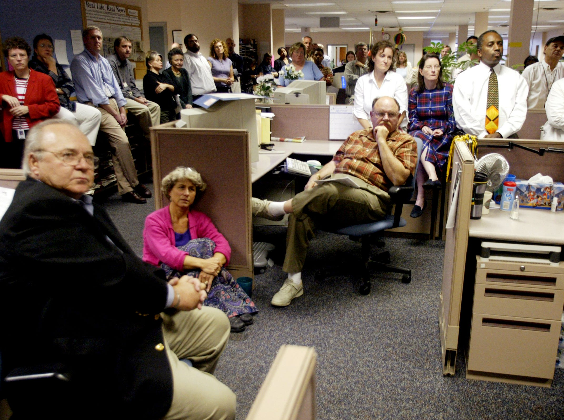 Tennessean staffers watch as editor Frank Sutherland announces his impending retirement at a back-of-the-newsroom meeting Sept. 8, 2004.
